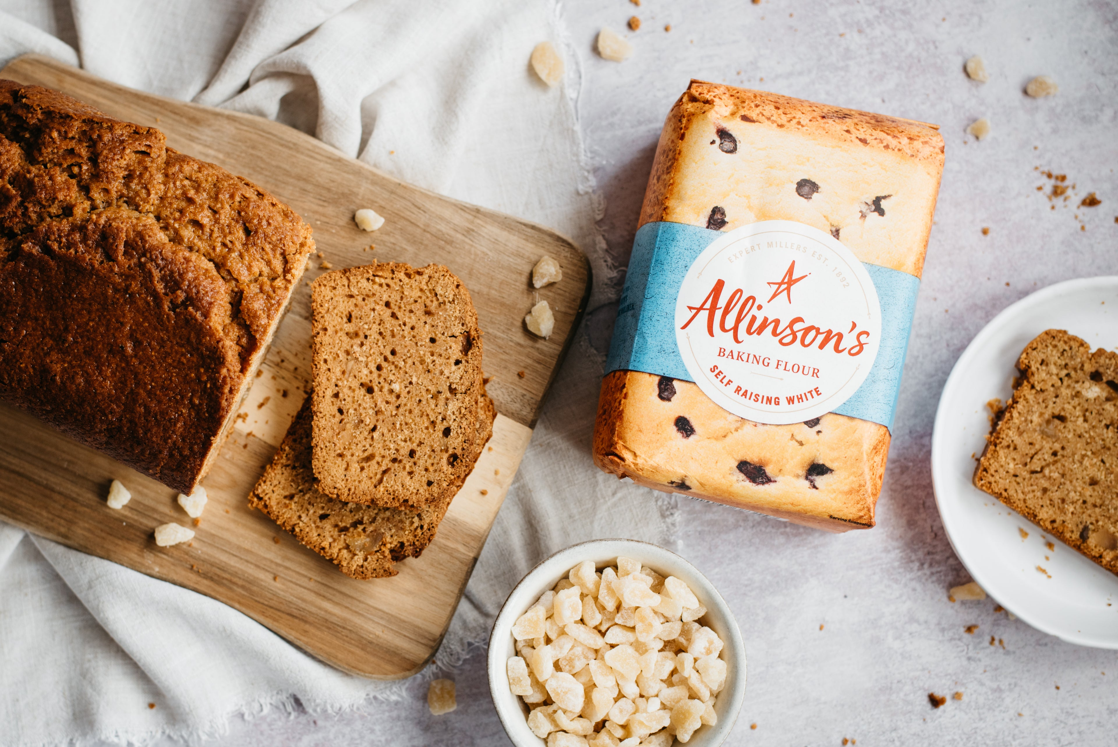 A flat lay of Gingerbread Loaf on a serving board, next to a bowl of ginger, bag of Allinson's flour and a slice of Gingerbread Loaf on a plate