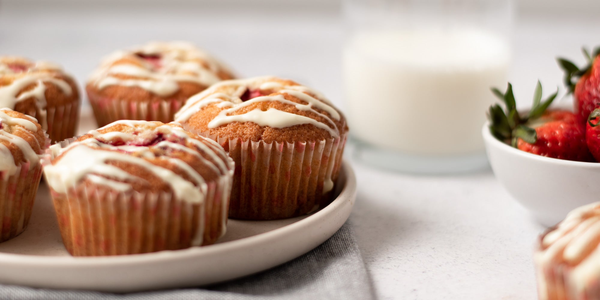 Cupcakes with a strawberry in the centre drizzled with white chocolate