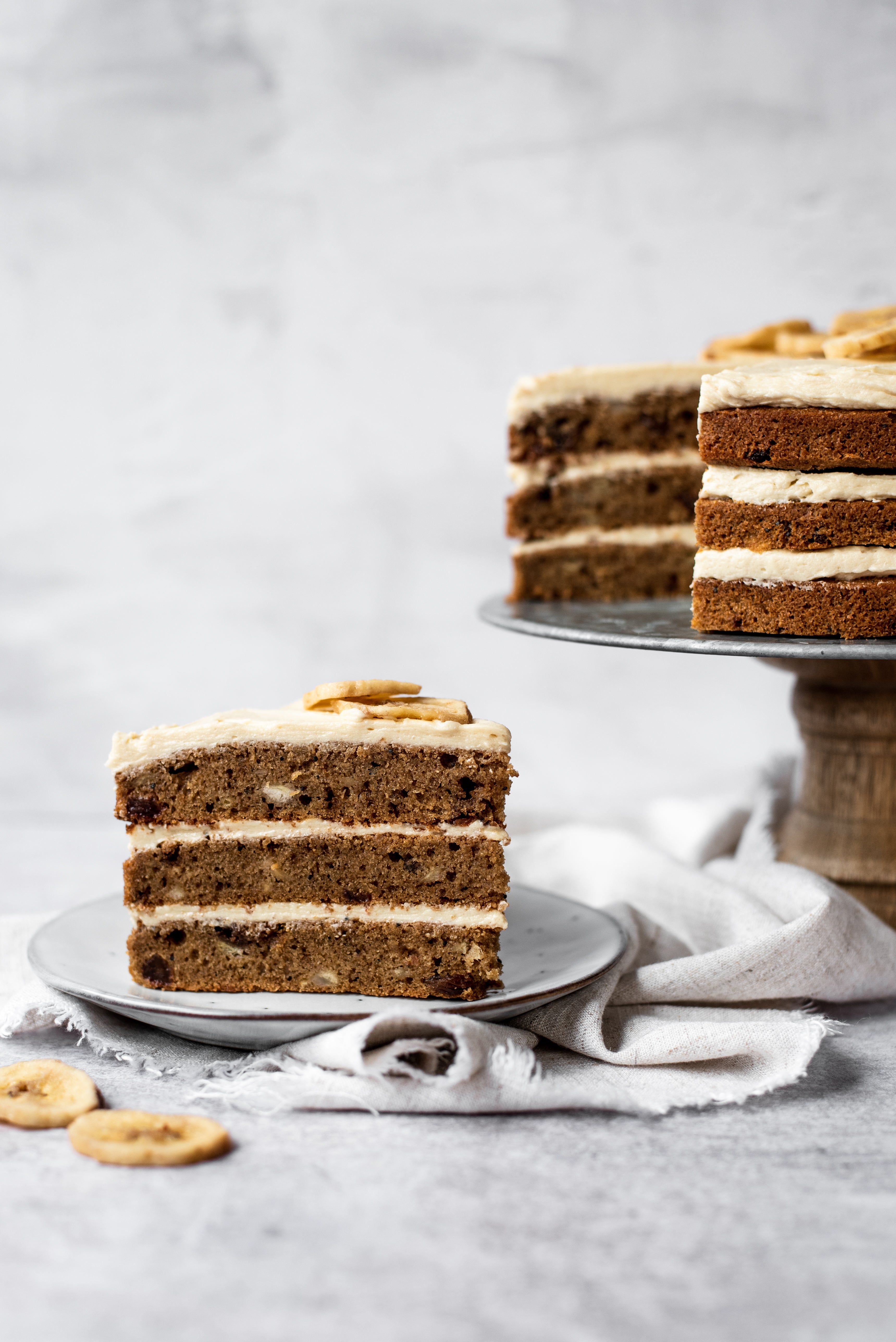 Slice of banana cake with 3 layers on a plate in front of remaining cake of cake stand
