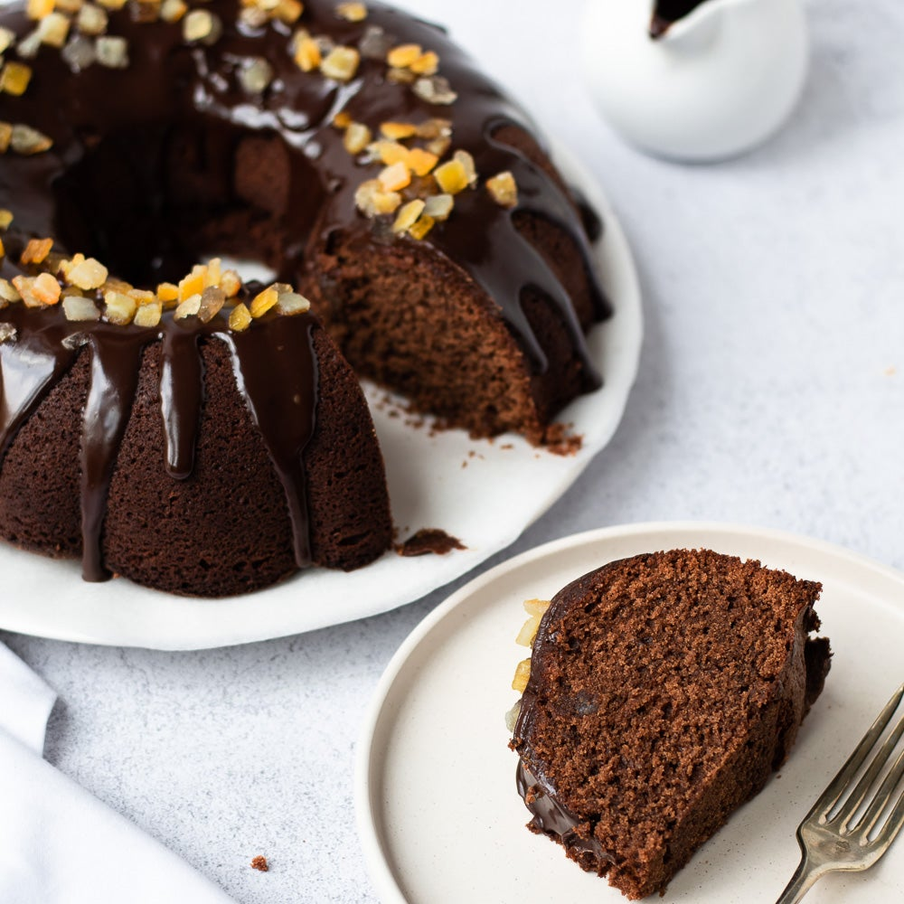 chocolate orange bundt cake on plate with chocolate drizzle on top with candid orange peel
