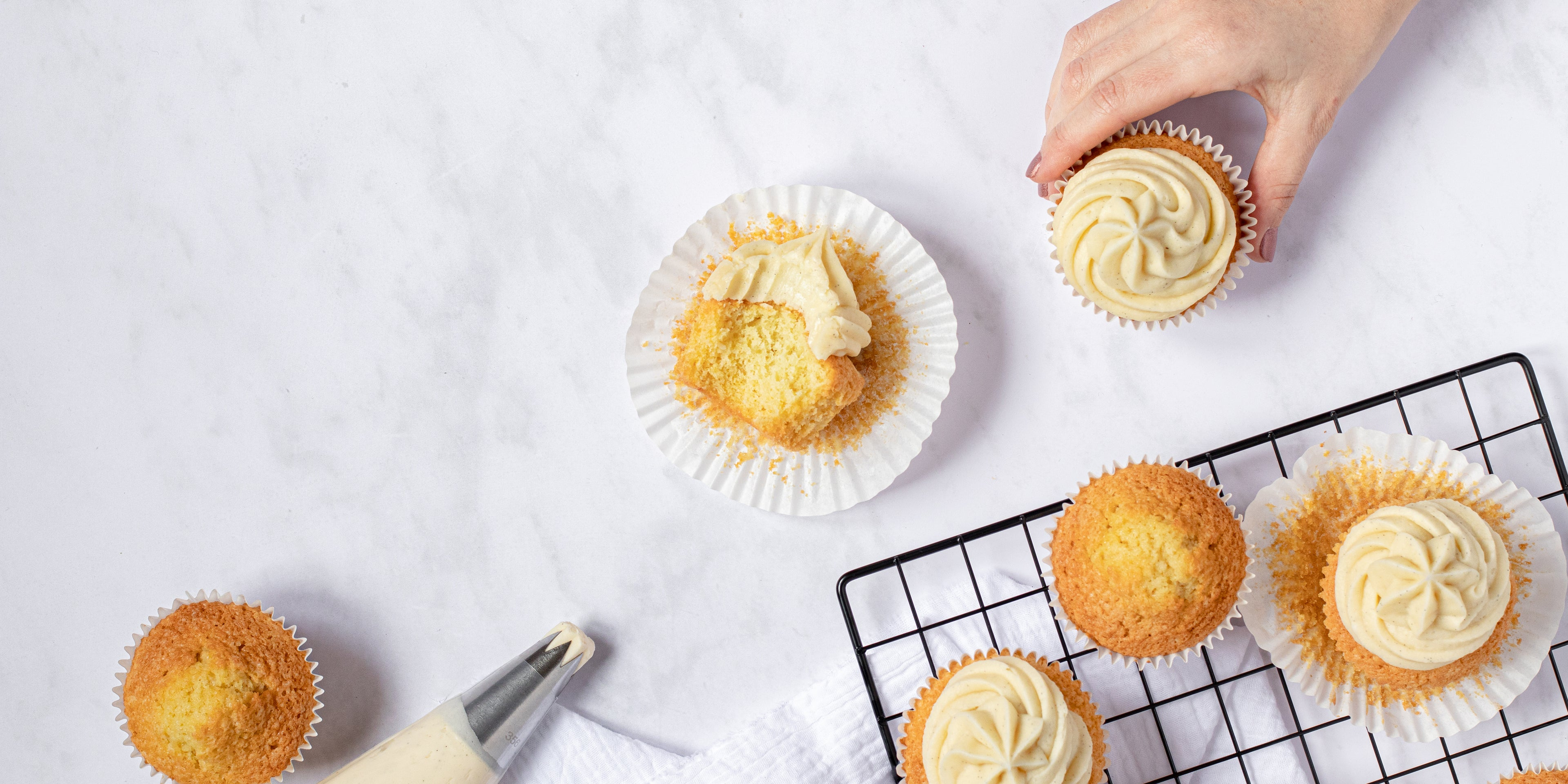 Vanilla cupcakes on a baking tray and table topped with vanilla buttercream