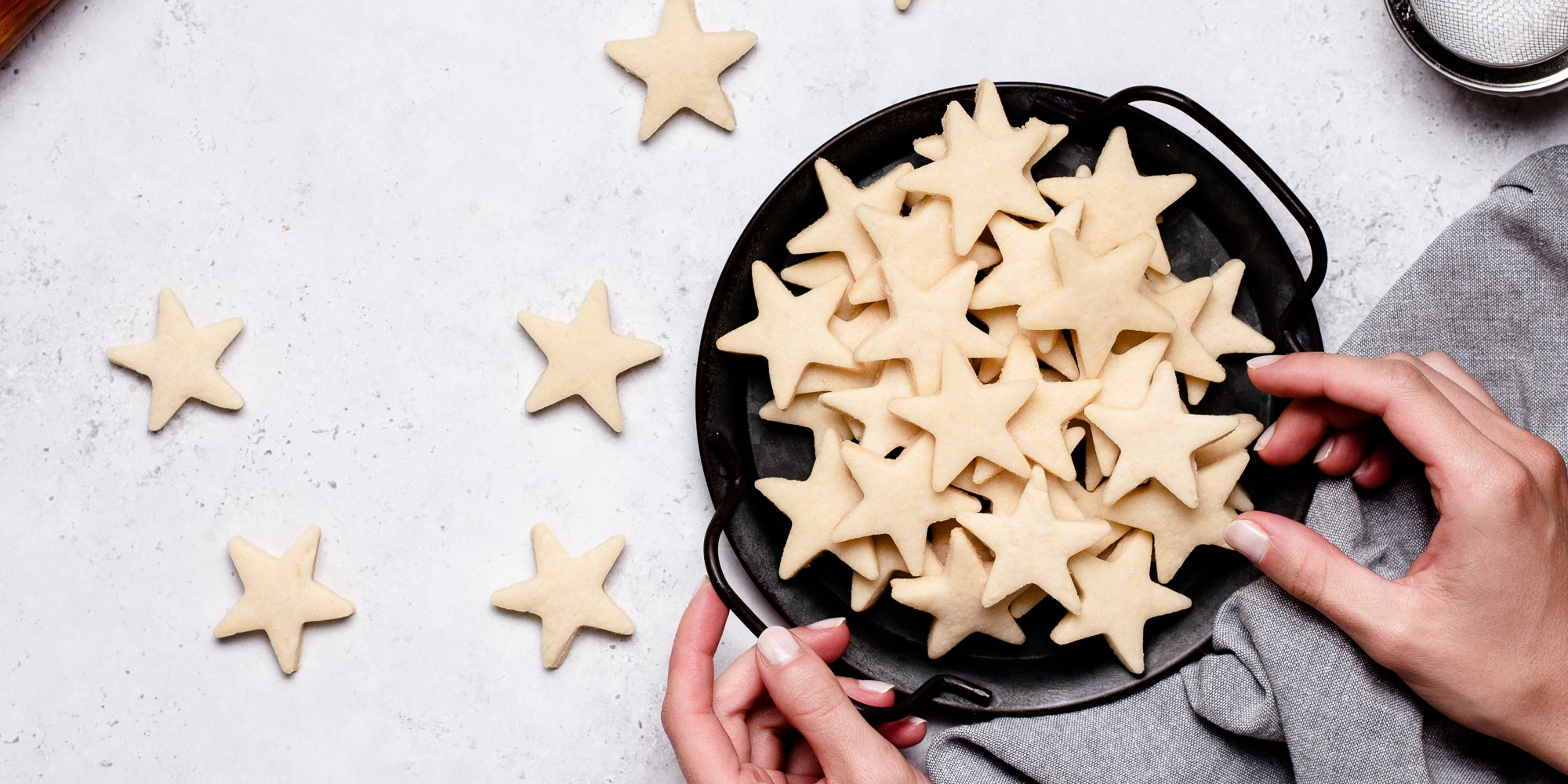 A top down view of a hand taking from some star shaped vegan biscuits in a bowl