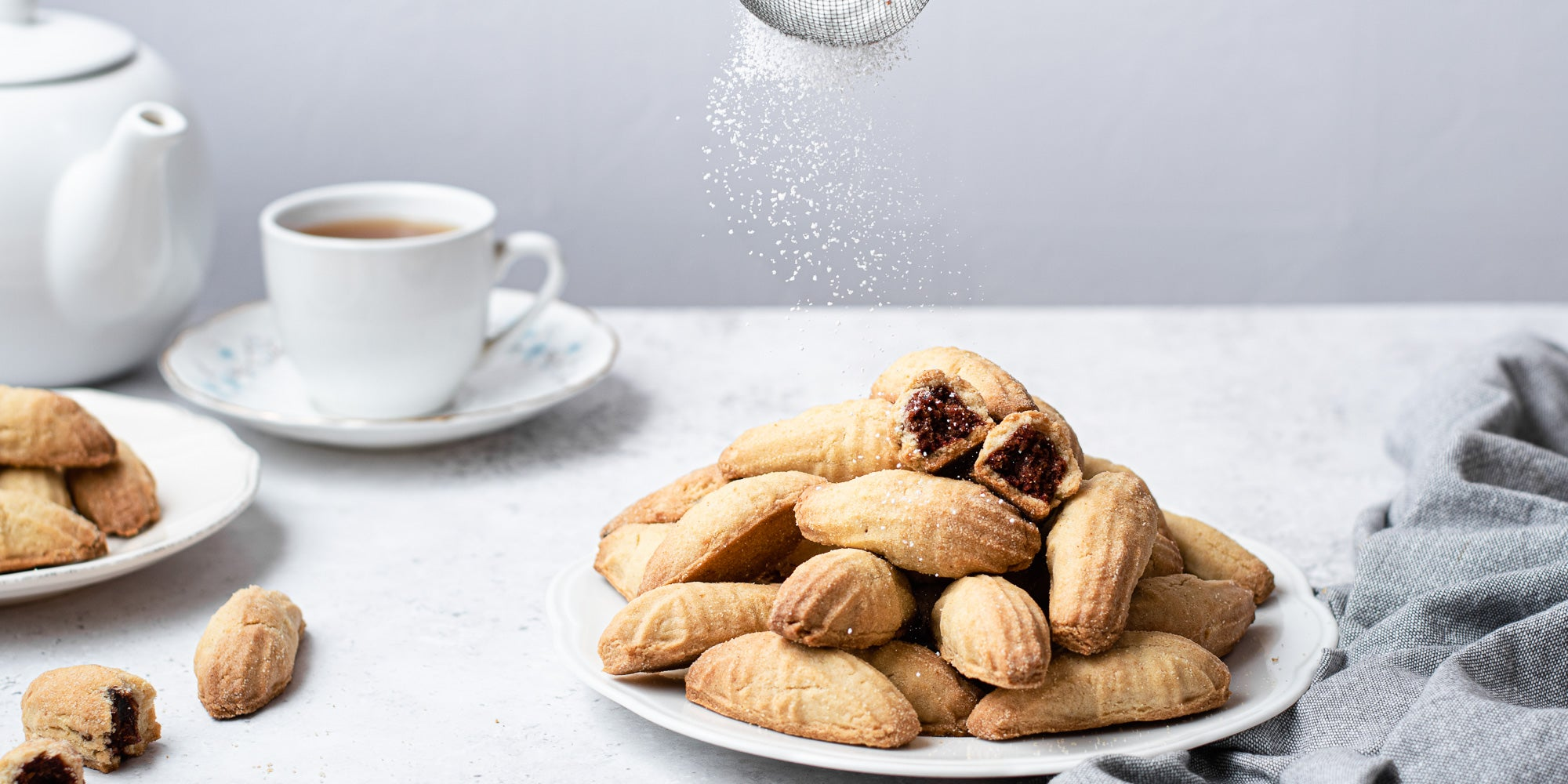 Two plates of Mamoul cookies on white plates, cup of tea in background and icing sugar dusted on top.
