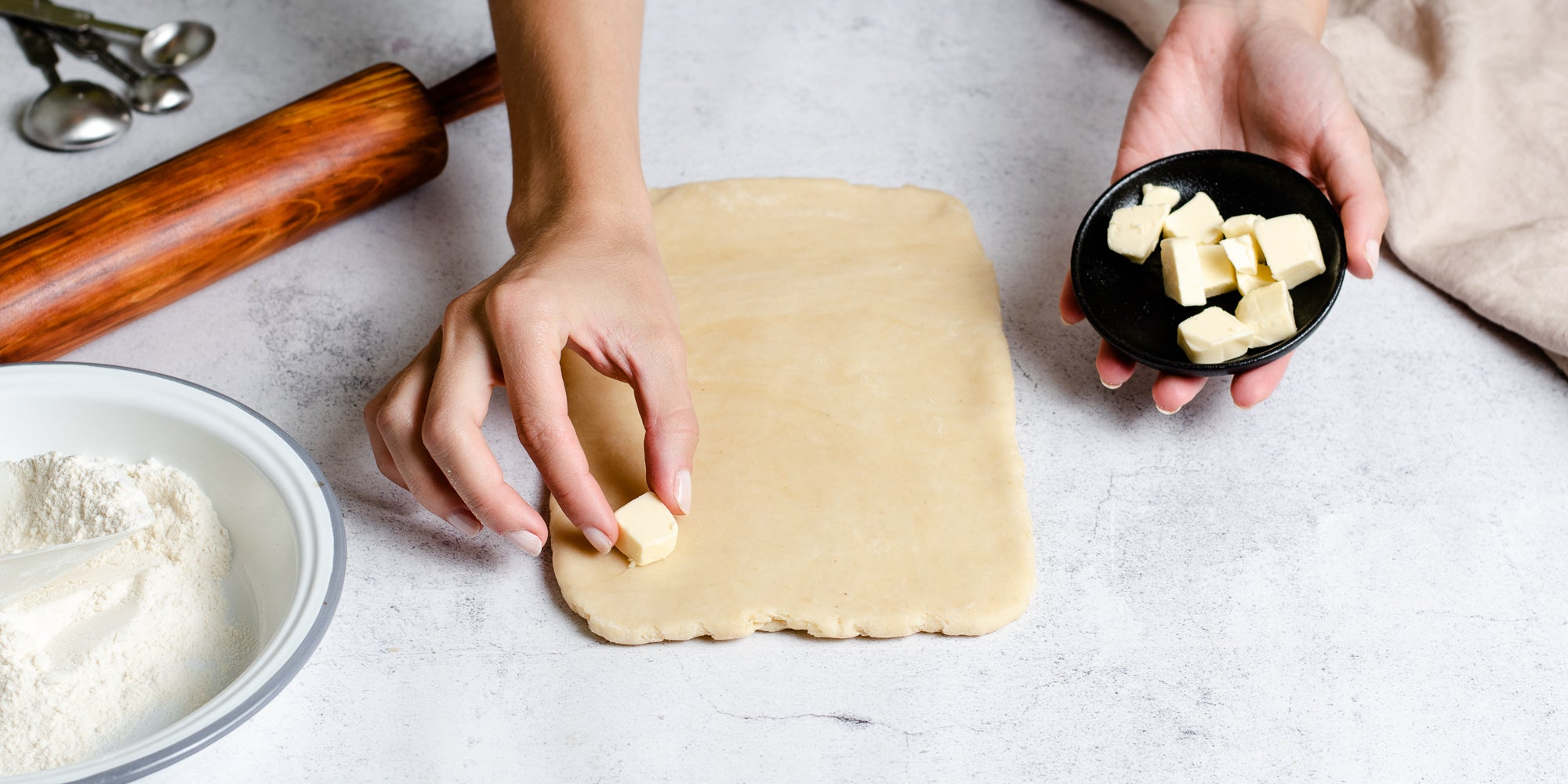 Hand laying out pieces of butter on rolled out Puff Pastry dough, ready to fold and roll out, next to a rolling pin and bowl of flour
