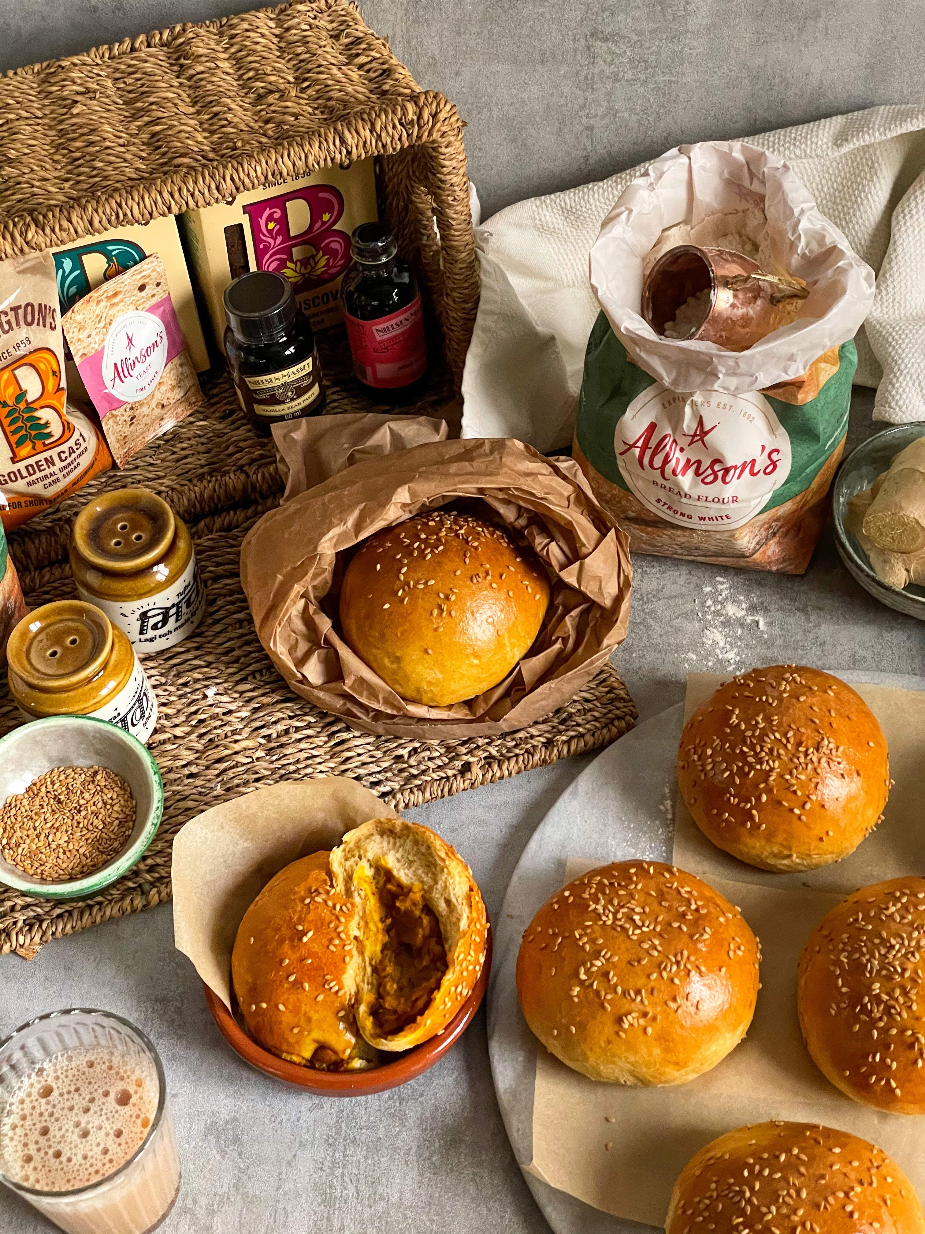 Top down view of spiced masala buns next to a hamper filled with baking ingredients