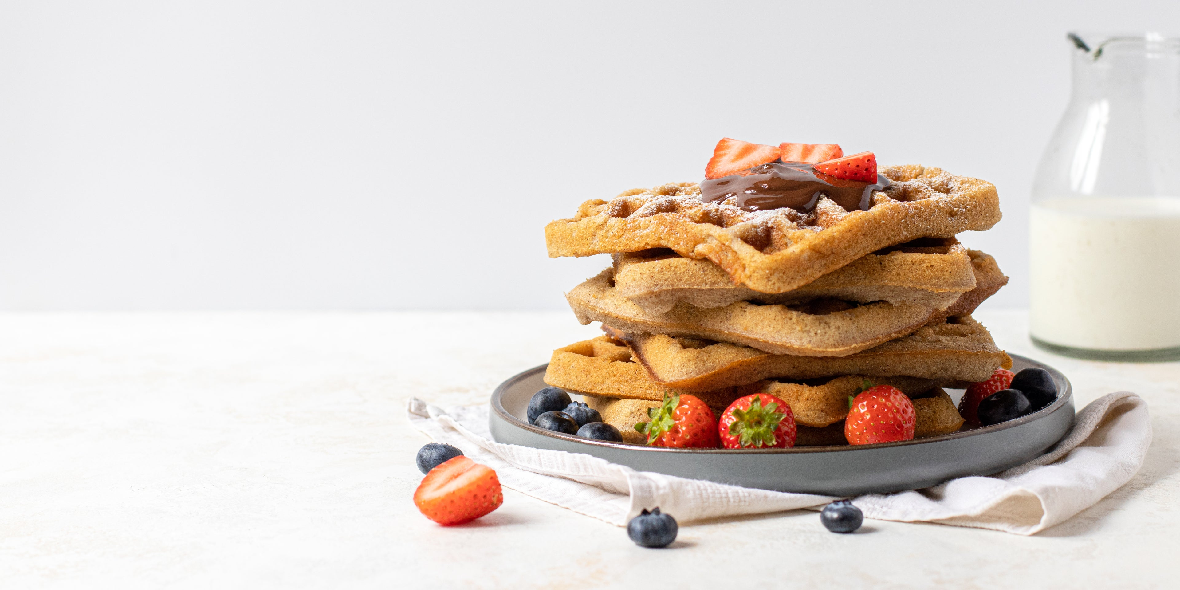 Stack of Waffles topped with berries, chocolate sauce and dusted with icing sugar