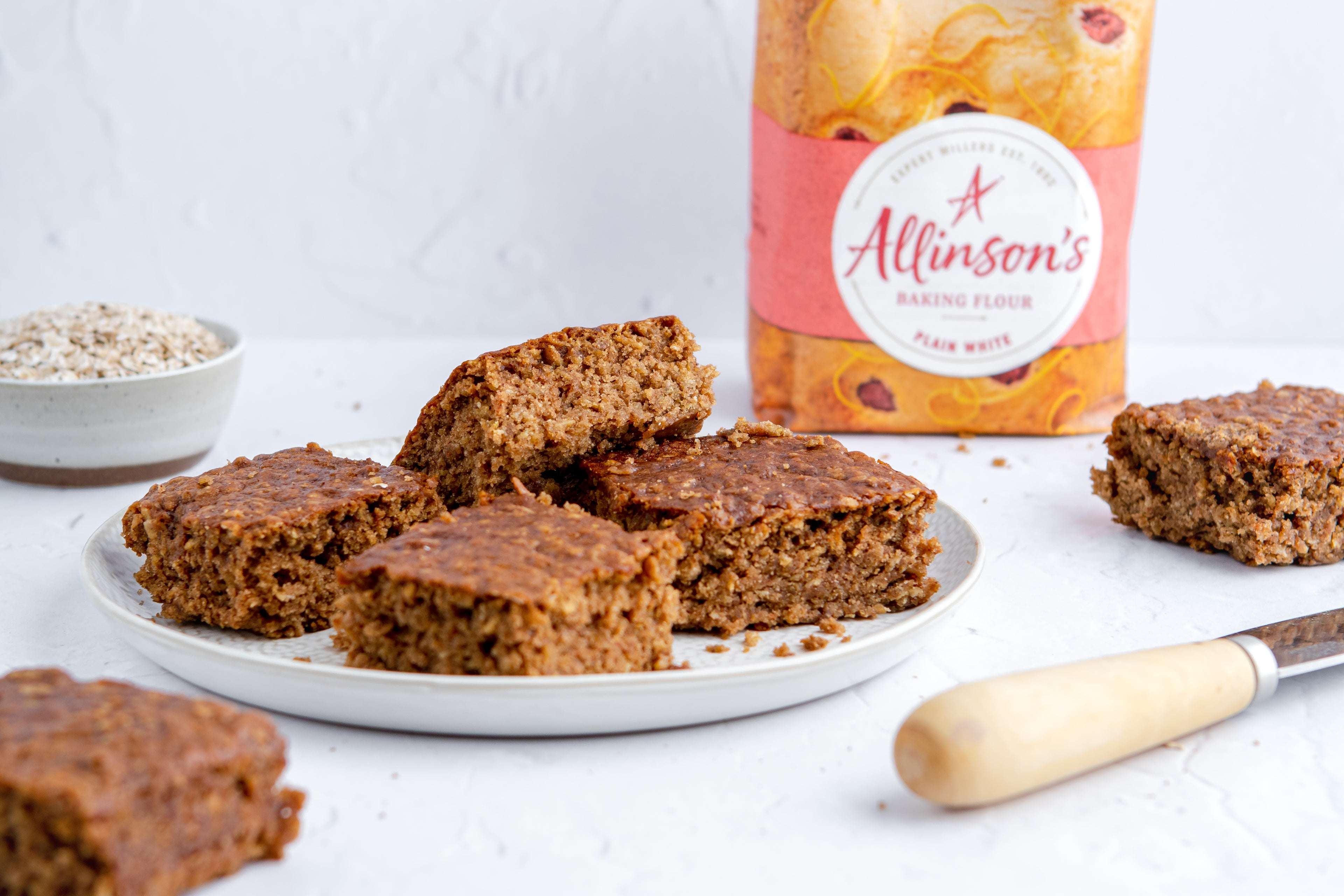 Sticky Yorkshire Parkin slices on a plate with Allinson's Plain White flour in the backgroun
