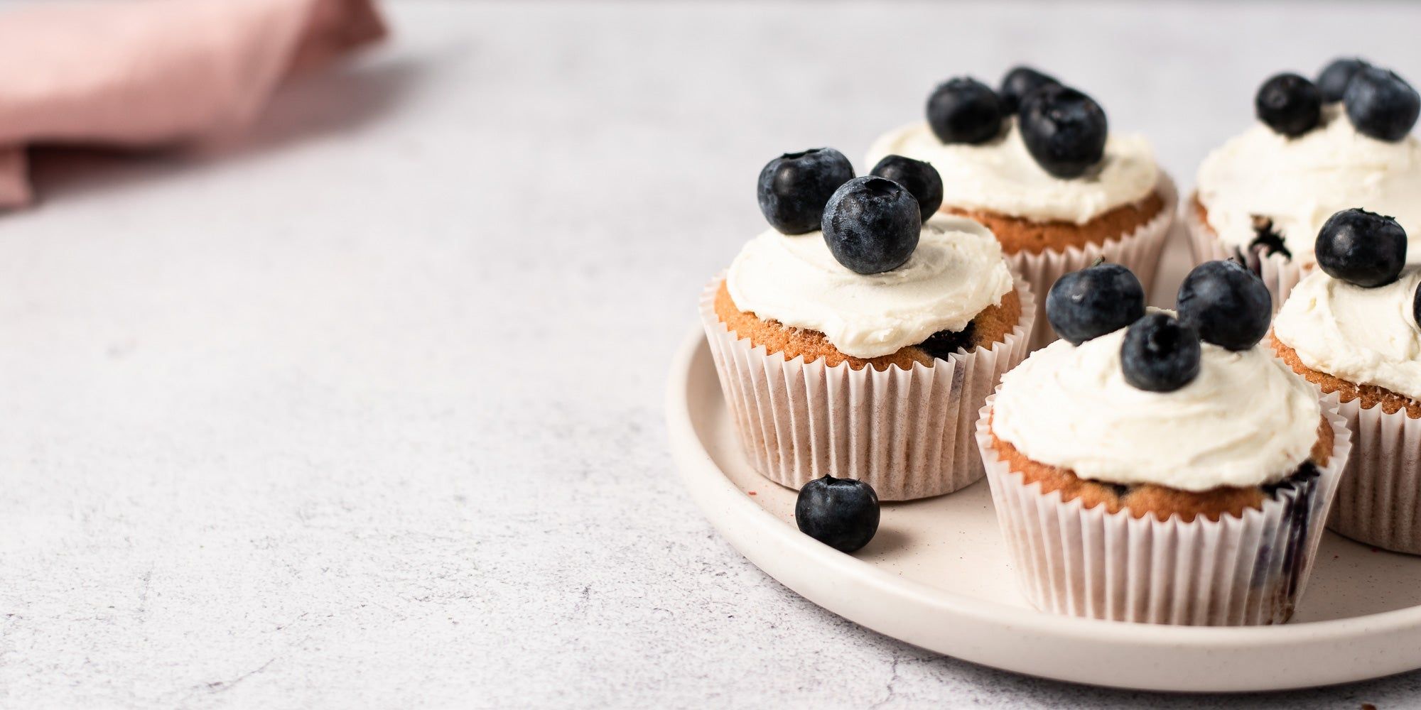 Cupcakes topped with icing and blueberries