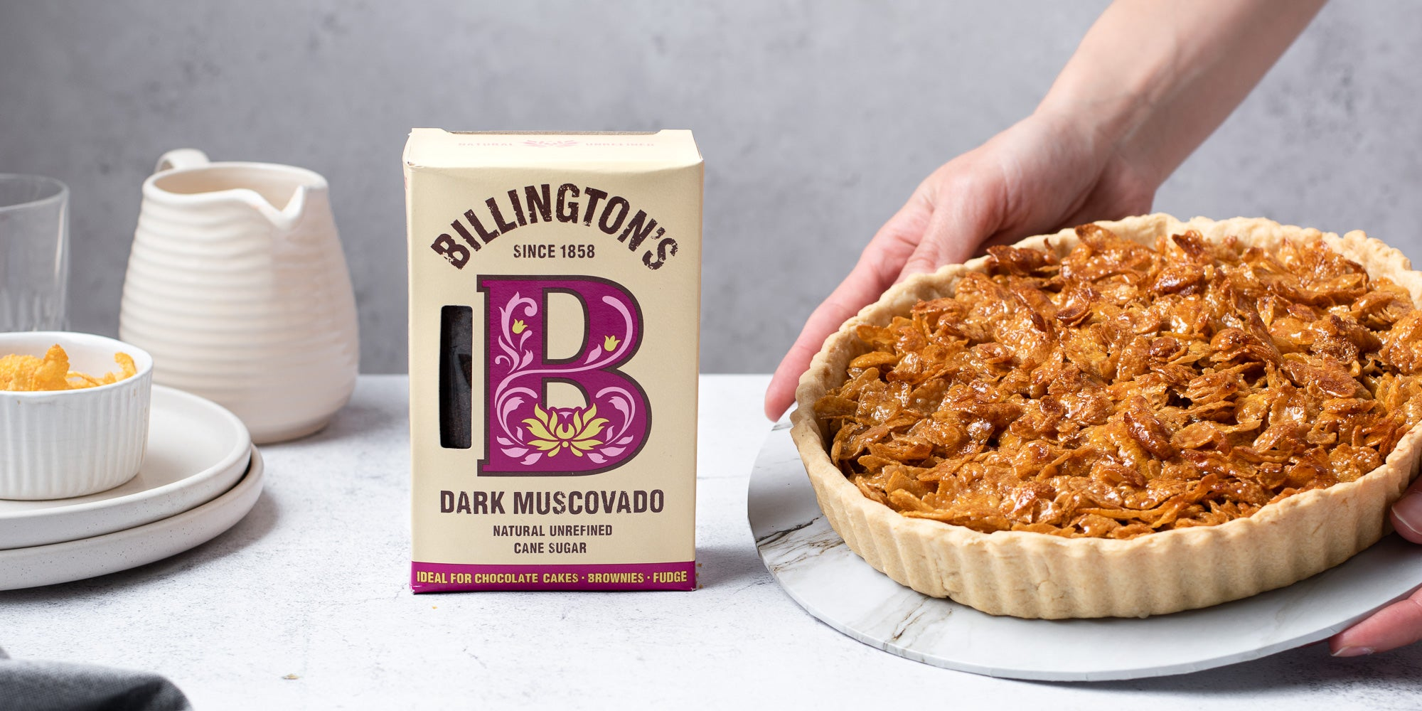 Cornflake Tart next to a box of Billington's Dark Muscovado sugar and a jug of custard