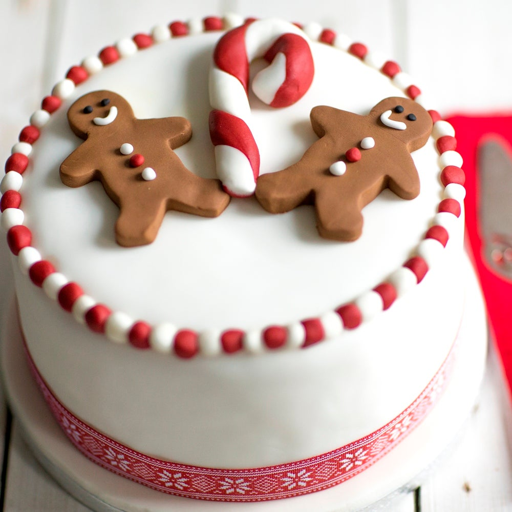 Christmas Cake decorated in white fondant with red ribbon and covered in fondant gingerbread men and candy canes