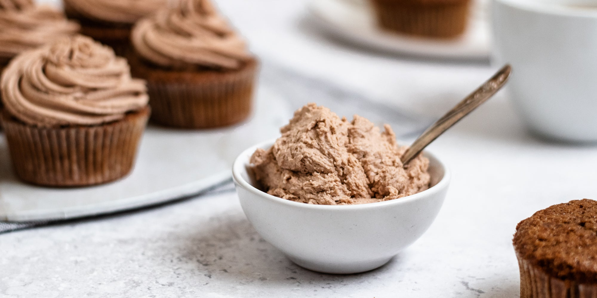 Close up of Dairy Free Vegan Chocolate Buttercream in a small bowl, with a spoon. Cupcakes topped with Dairy Free Vegan Chocolate Buttercream in the background