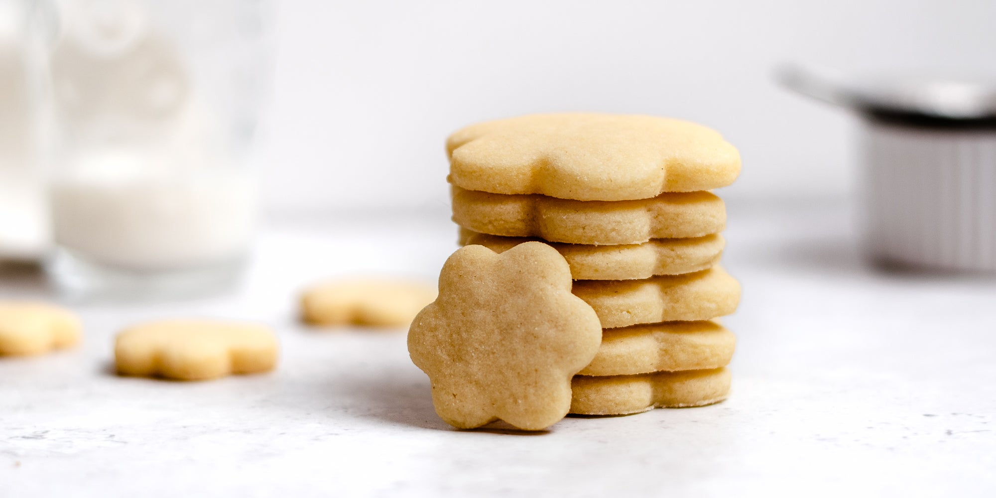Close up of a stack of biscuits baked with the Basic Biscuit Dough recipe, with a glass of milk in the background
