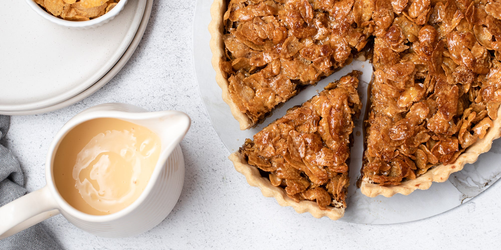 Overhead shot of cornflake tart with slice removed and jug of custard