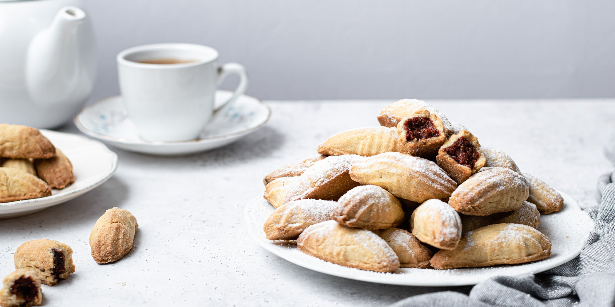 Mamoul cookies dusted with icing sugar, next to a pot of tea