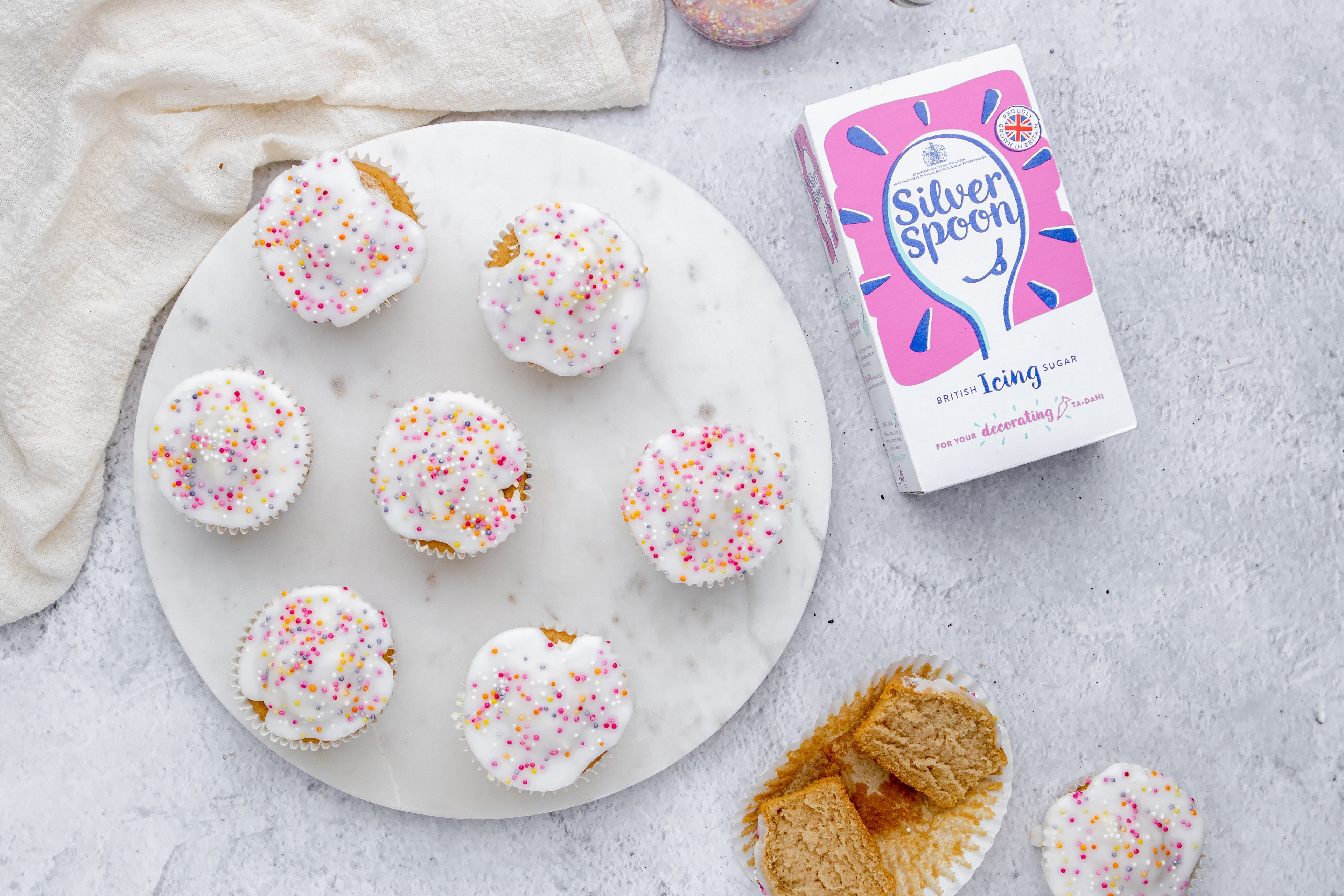 Simple Fairy Cakes on a plate next to a box of Silver Spoon Icing Sugar, and a sliced cupcake in a cupcake case