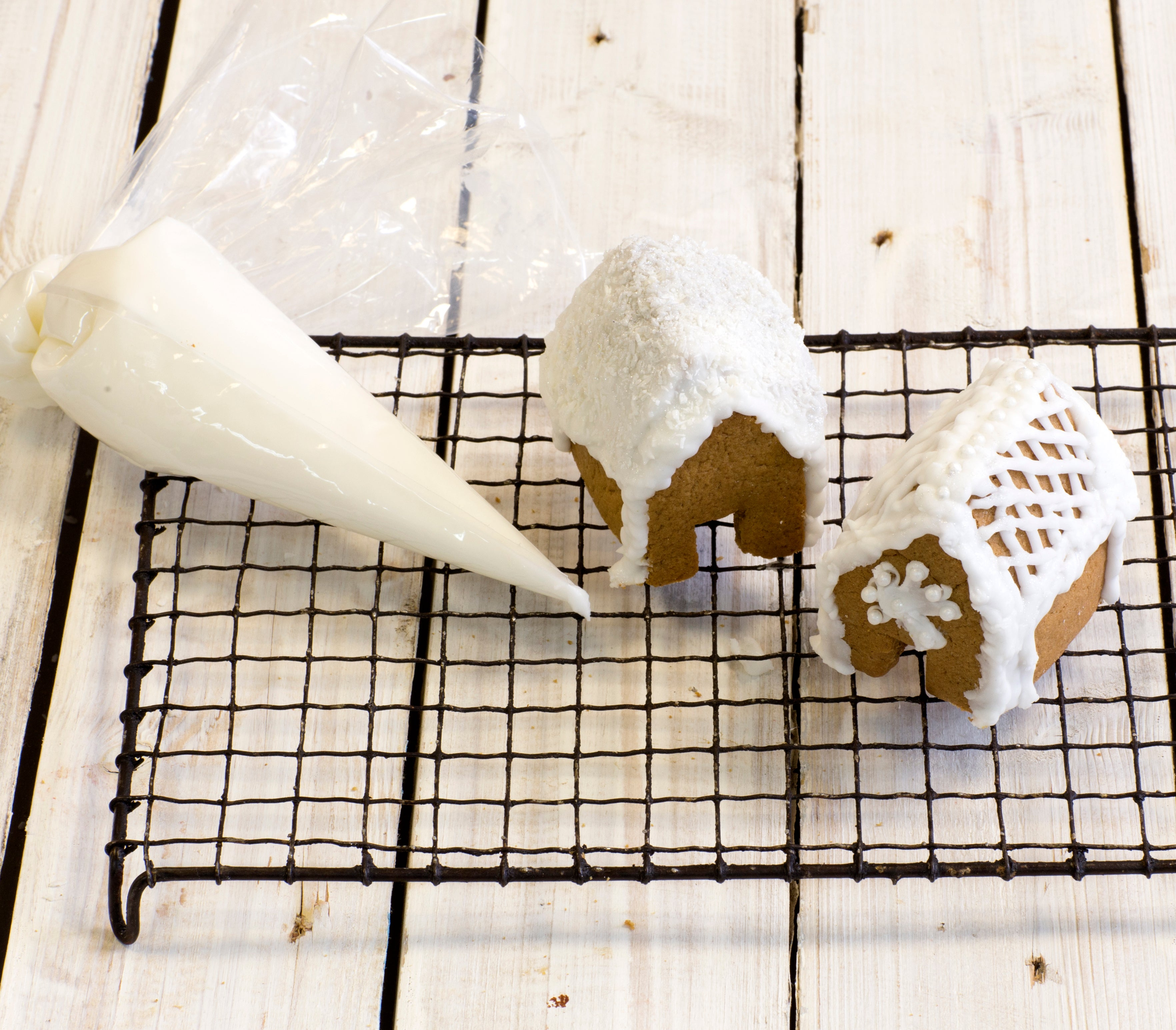 Gingerbread house construction with icing bag on cooling rack