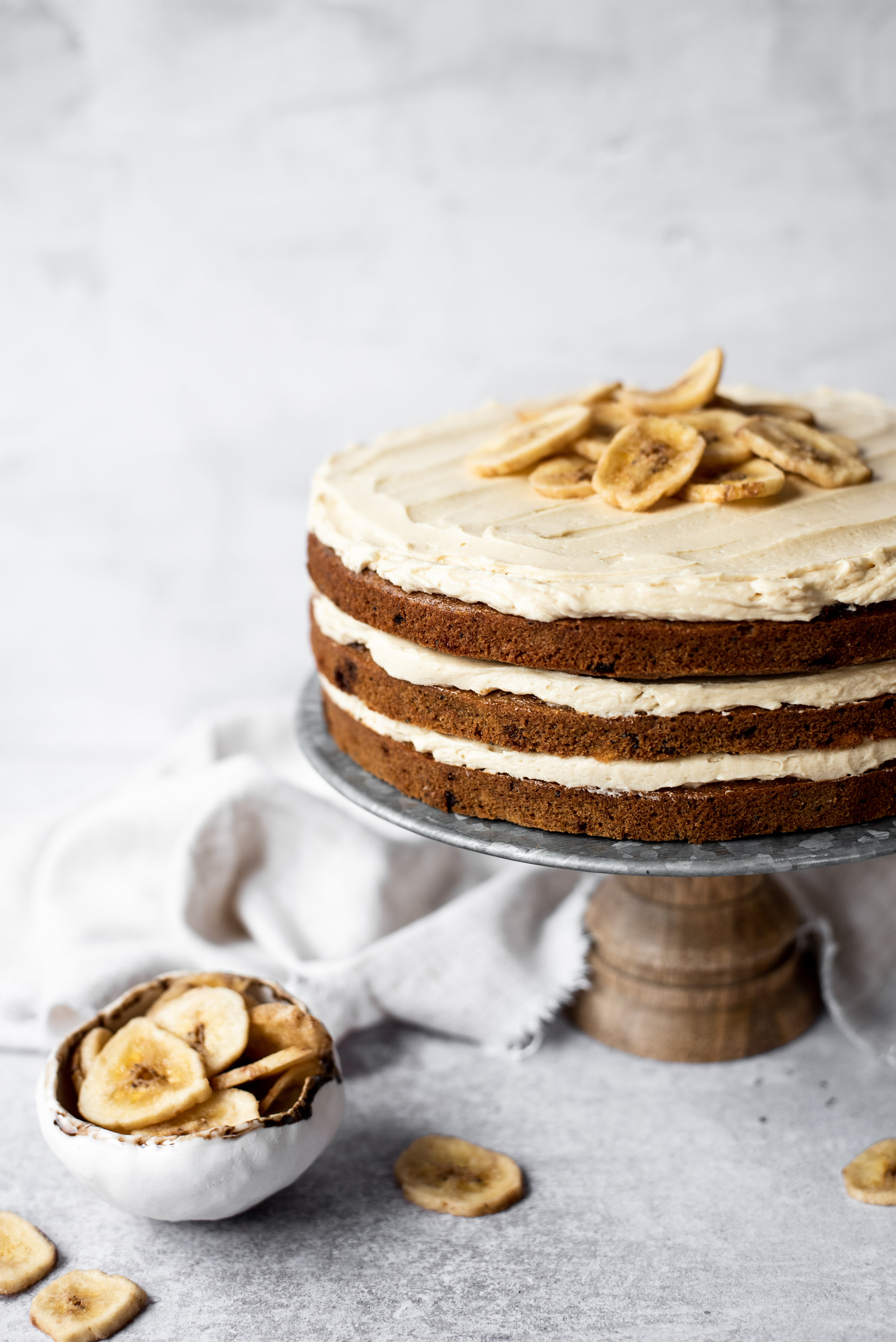 Banana Layer Cake with three layers on a cake stand with a bowl of banana chips