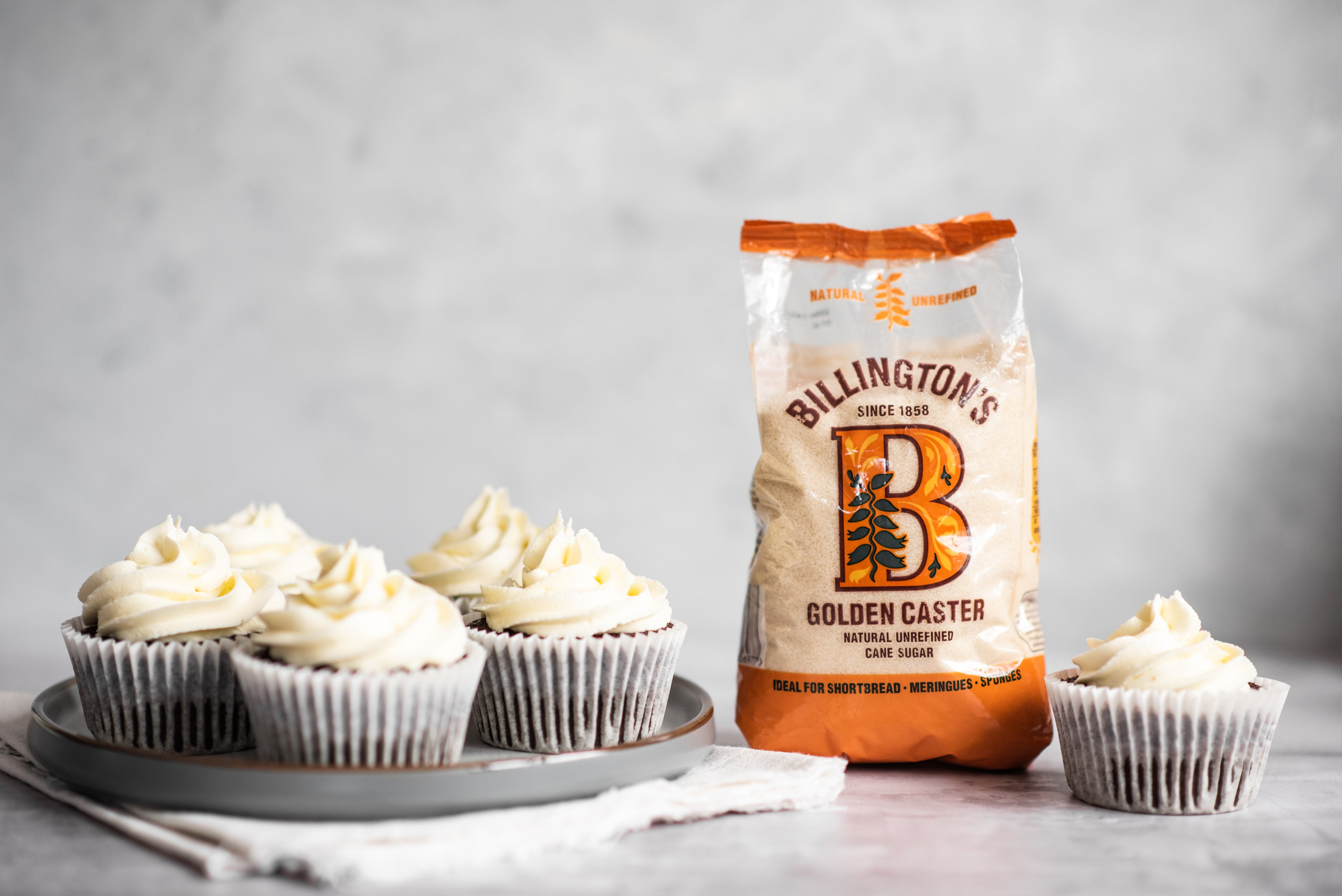 Cupcakes with a bag of sugar next to it