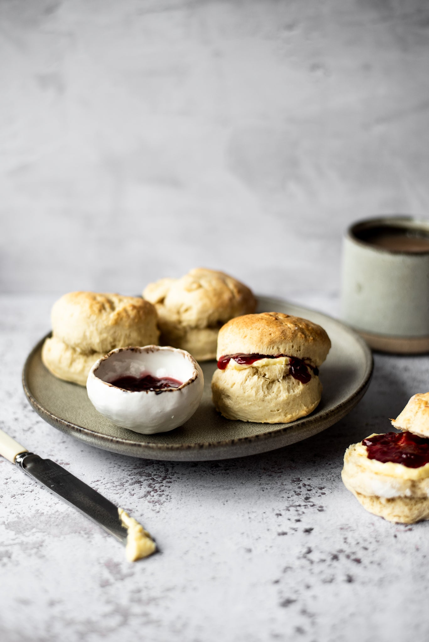 Three scones on a plate filled with jam and cream with pot of jam and knife with cream