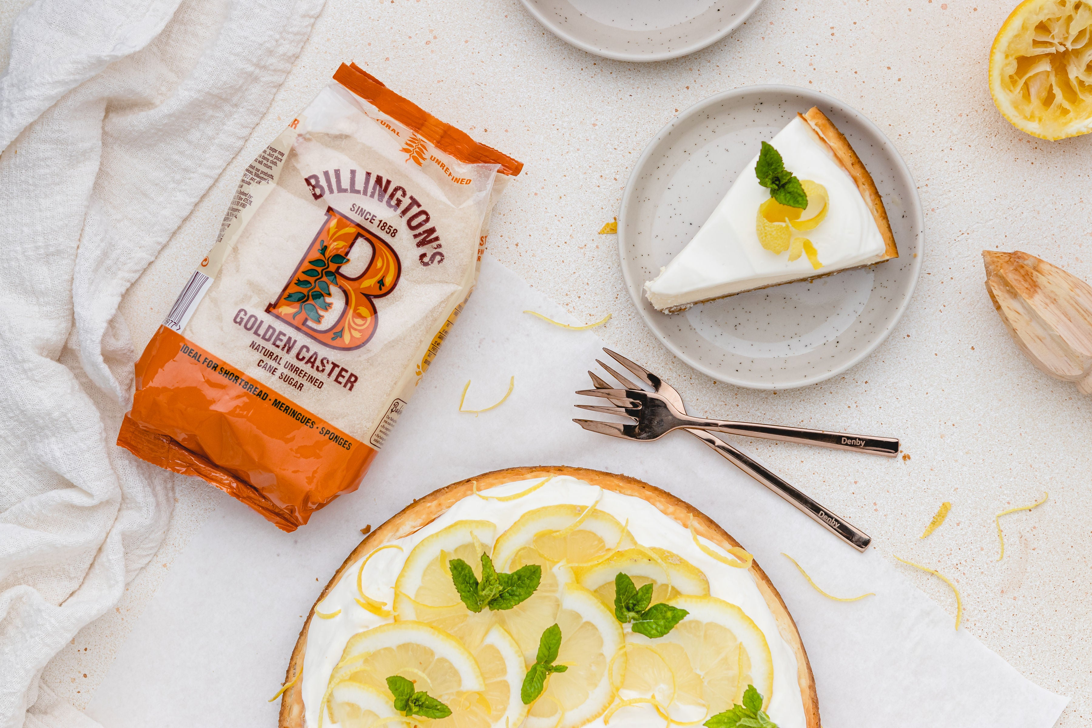 Slice of lemon cheesecake on plate, two forks and bag of sugar
