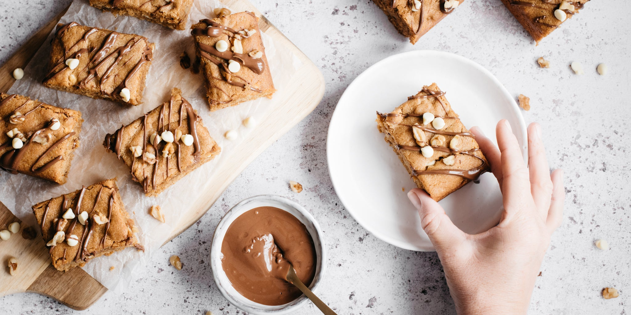 Overhead shot of peanut butter blondies cut into squares. One on a white plate with a hand reaching in. Pot of melted chocolate and a spoon