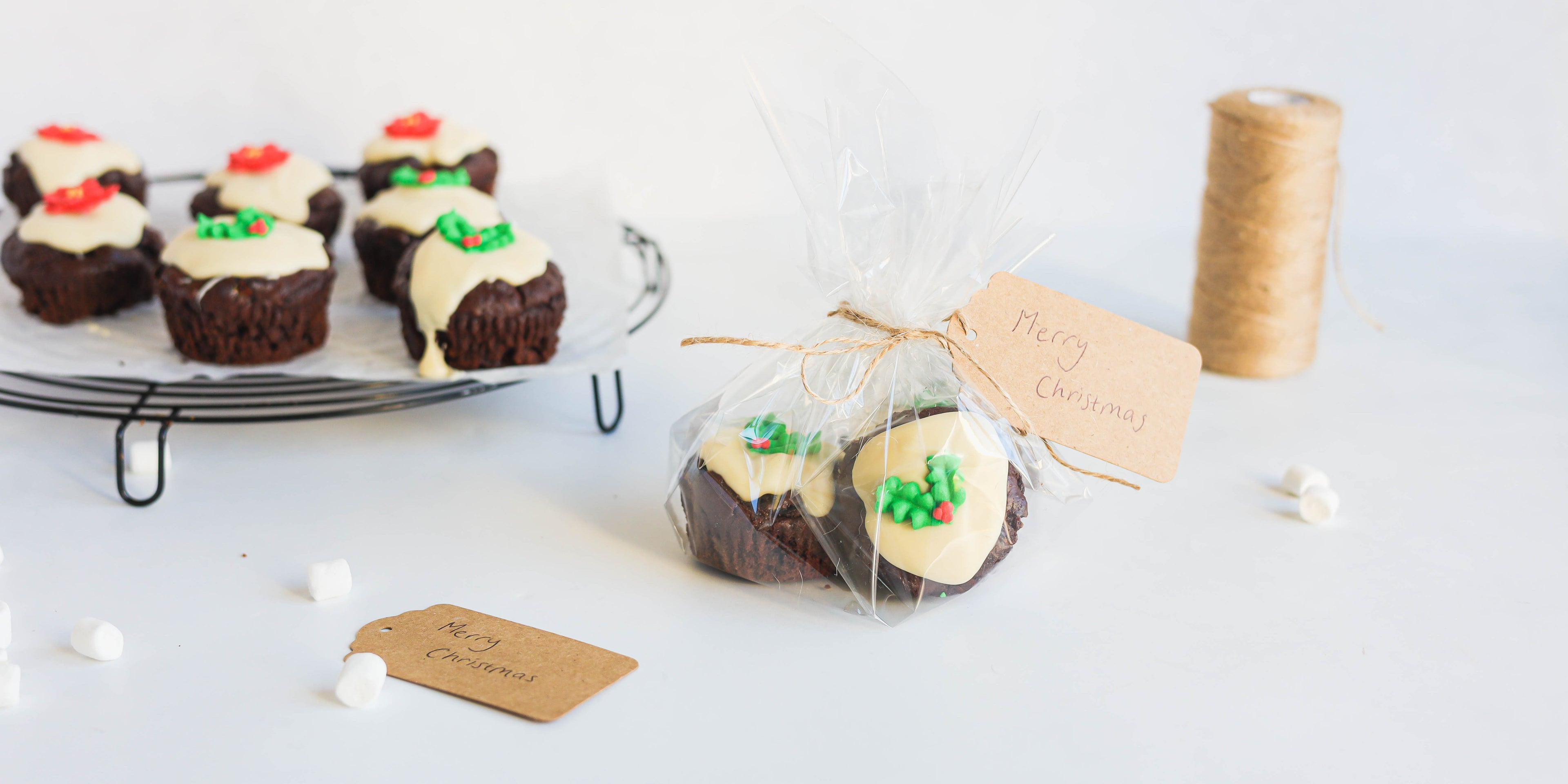 Mini Rocky Road Christmas Pudding Muffins on a wire rack, with a package of Mini Rocky Road Christmas Pudding Muffins hand tied in the foreground with a handwritten Christmas gift greeting