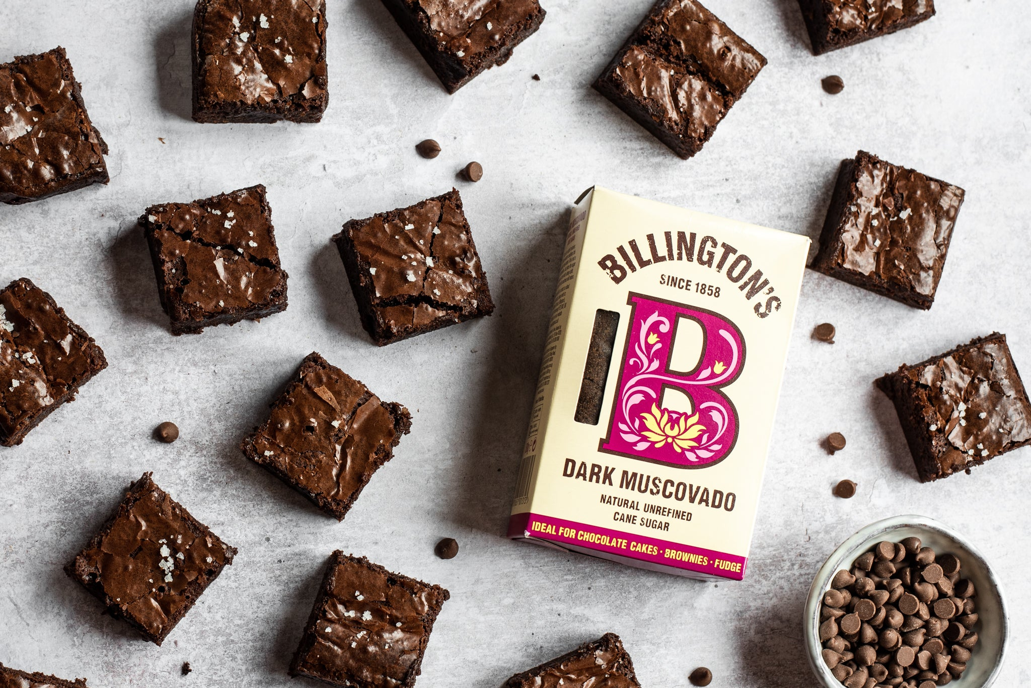 A top down view of chocolate brownies next to a packet of billingtons dark muscovado sugar