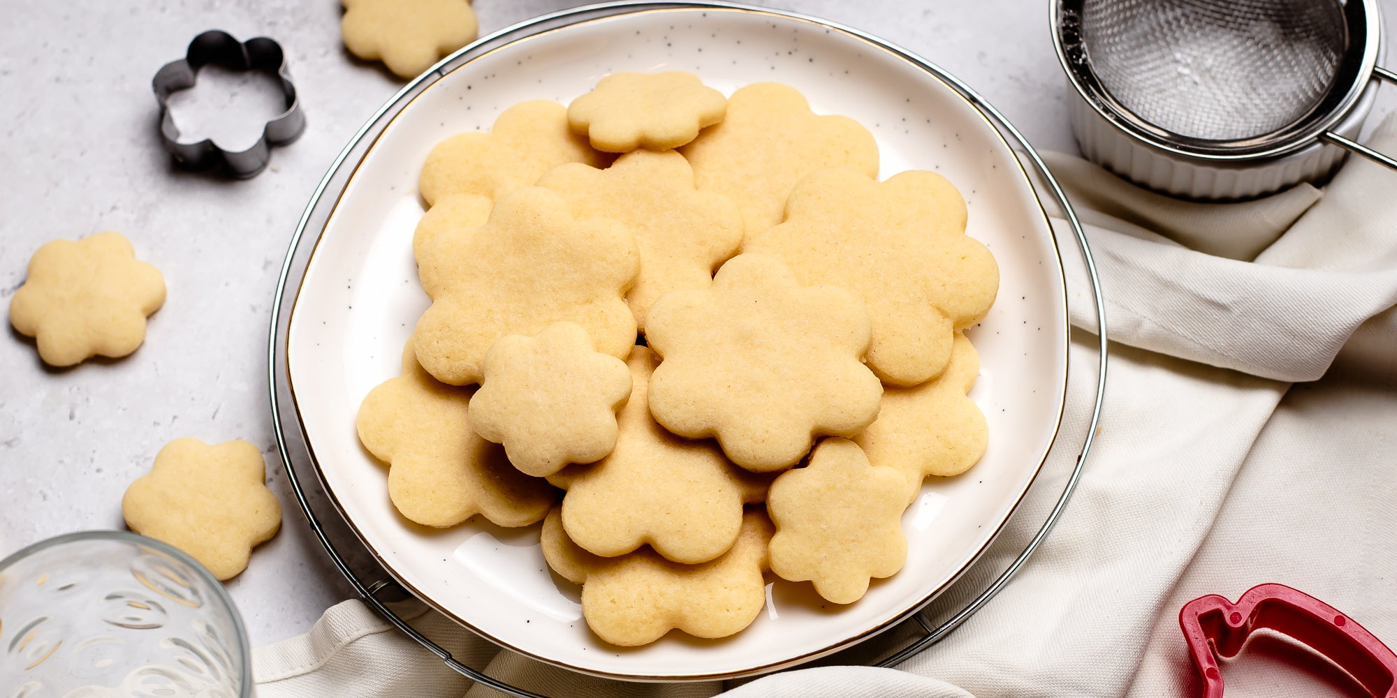 Biscuits baked with the Basic Biscuit Dough recipe, on a plate next to biscuit cutters and a sieve