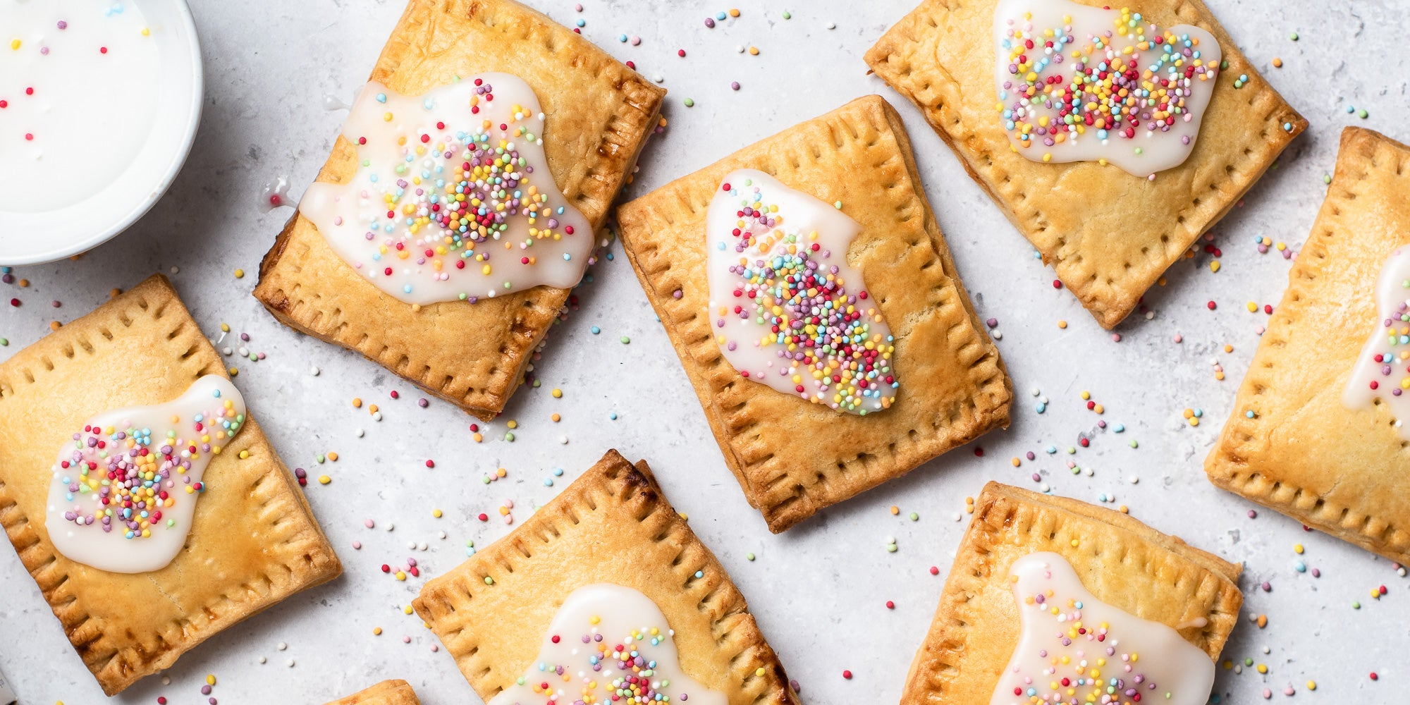 Homemade Pop Tarts with icing and sprinkles. Sprinkles scattered