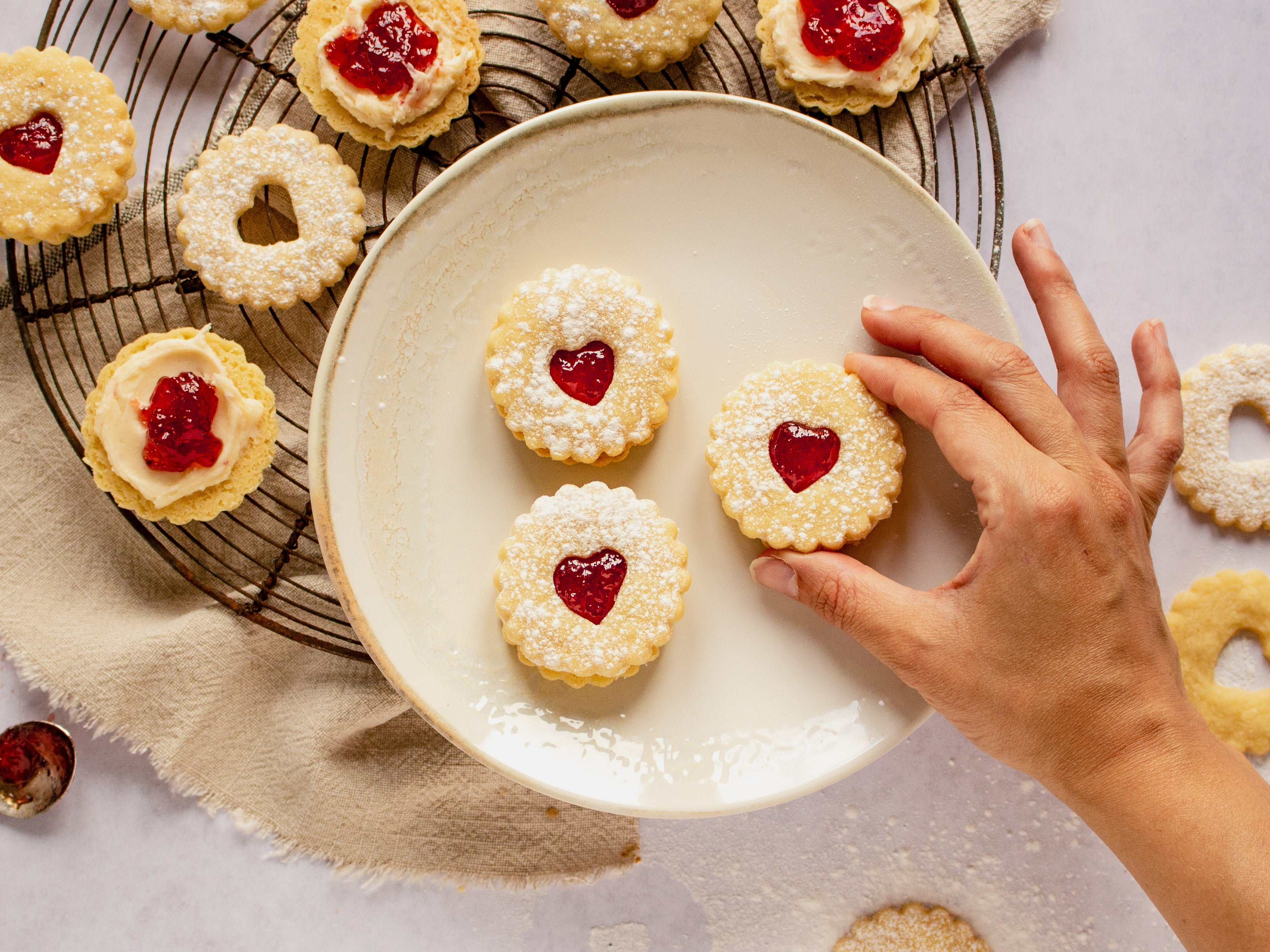 3 Jammy Dodgers on white plate with hand reaching in. Pulled apart biscuits on cooling rack