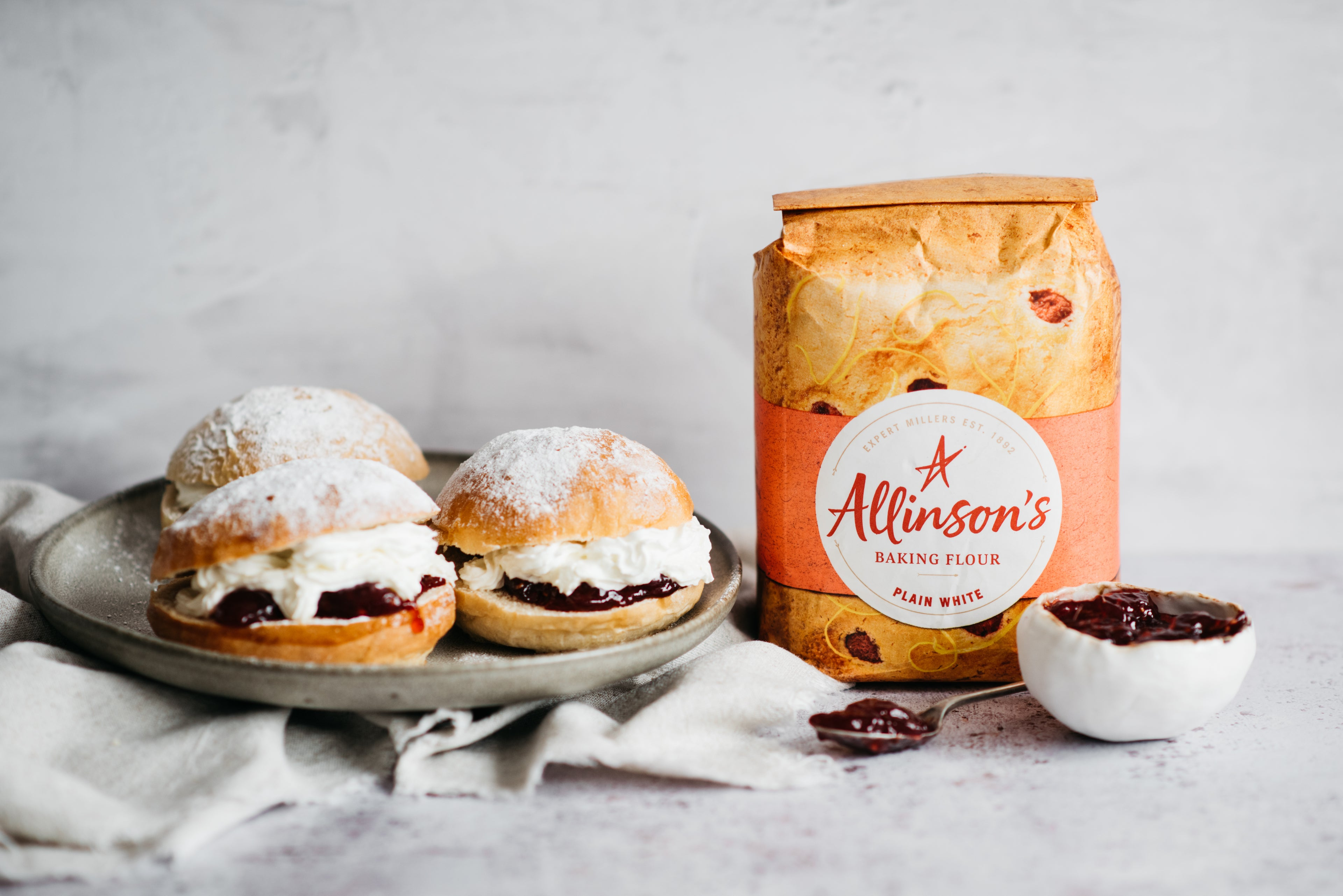 Plate of Devonshire Splits next to a bag of Allinson's plain white flour, with a bowl of jam and a spoon