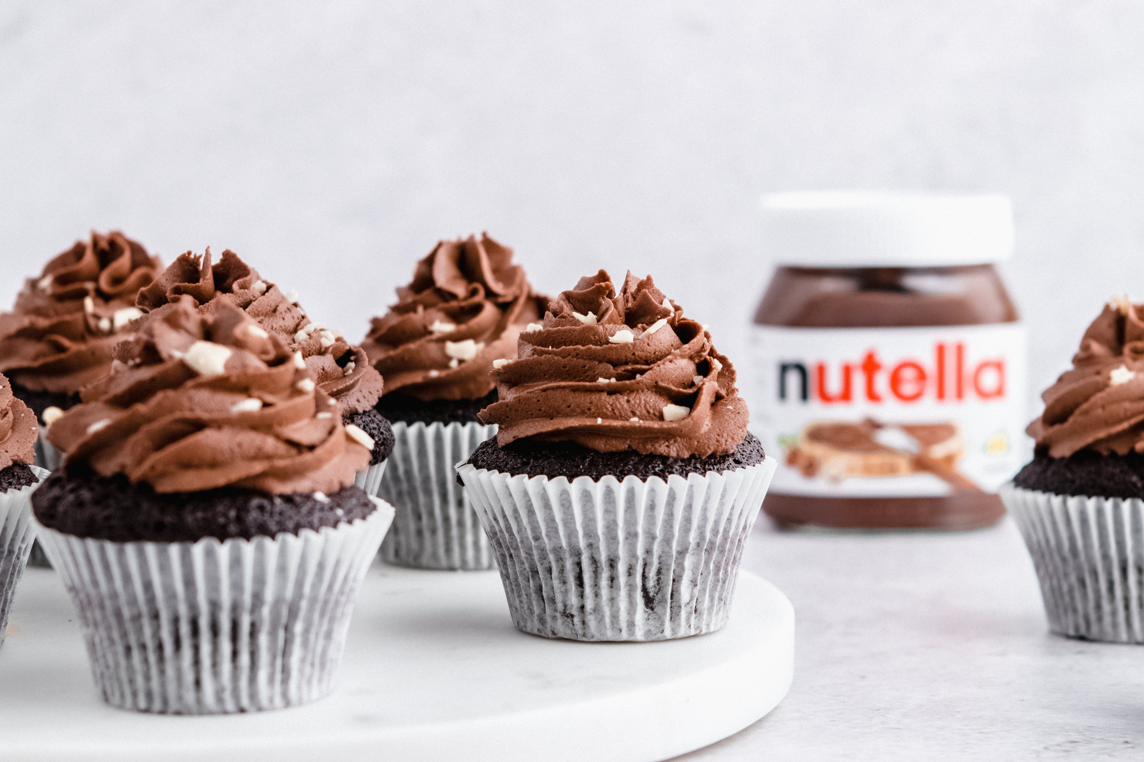Nutella cupcakes on a marble tray, with a jar of Nutella in the background