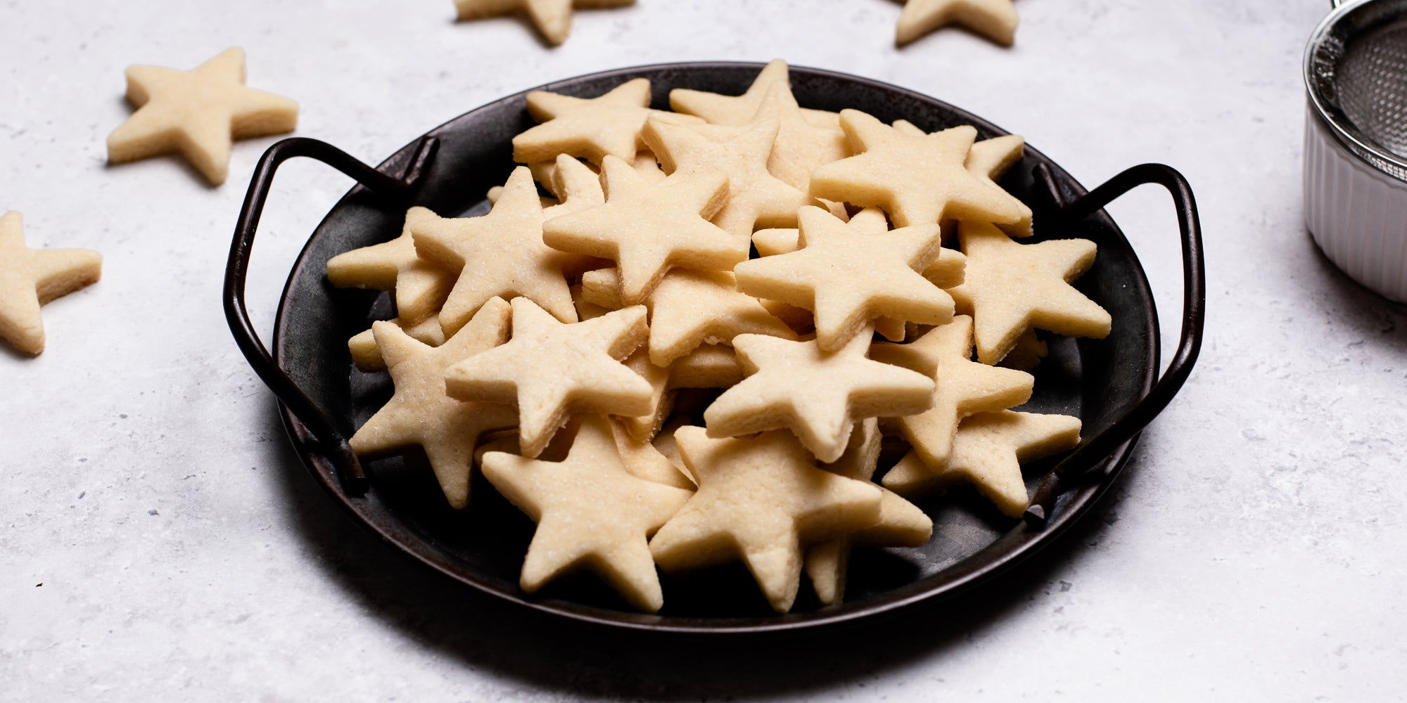 A side on view of star shaped vegan biscuits in a bowl
