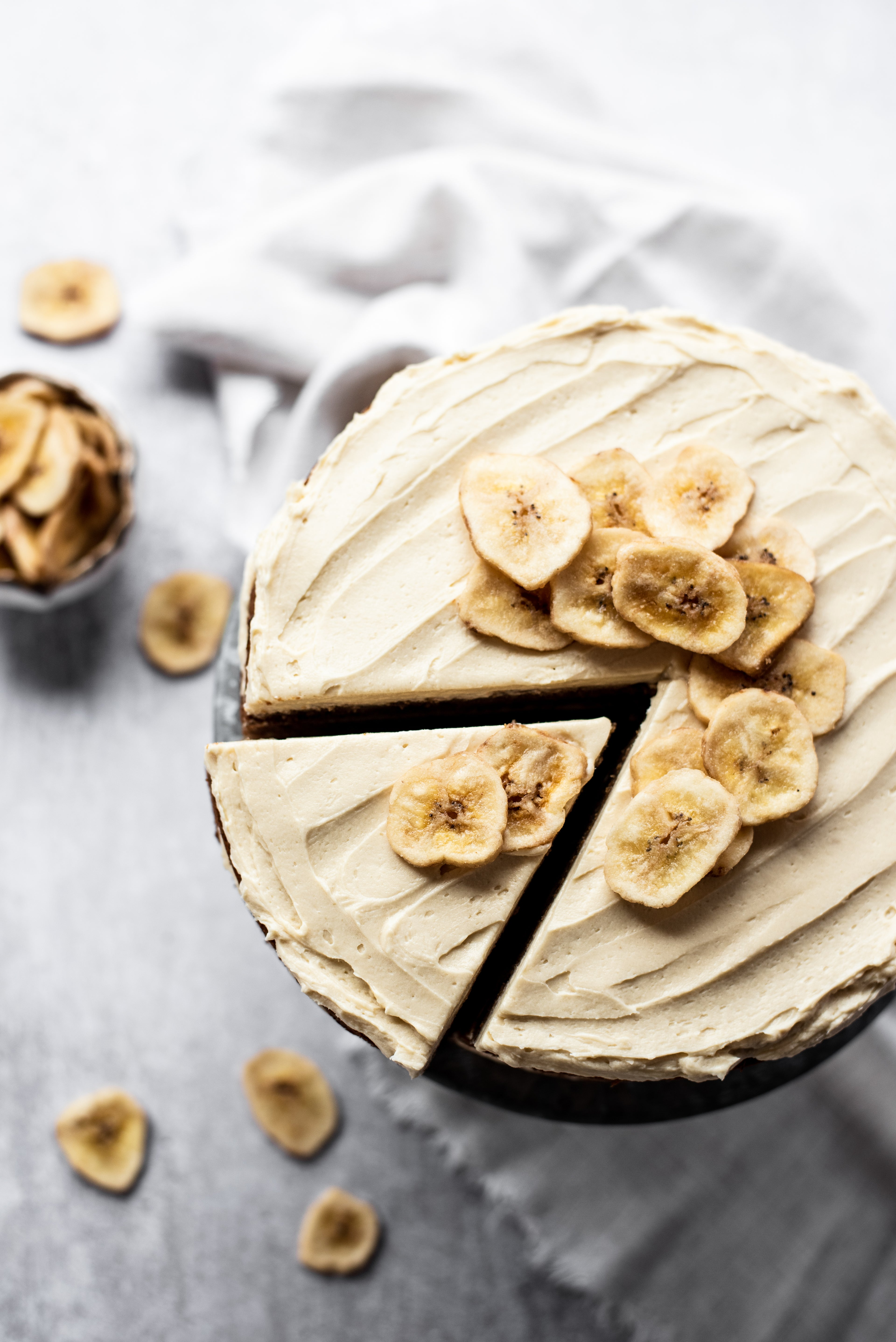 Top down image of banana layer cake with slice cut and topped with banana chips