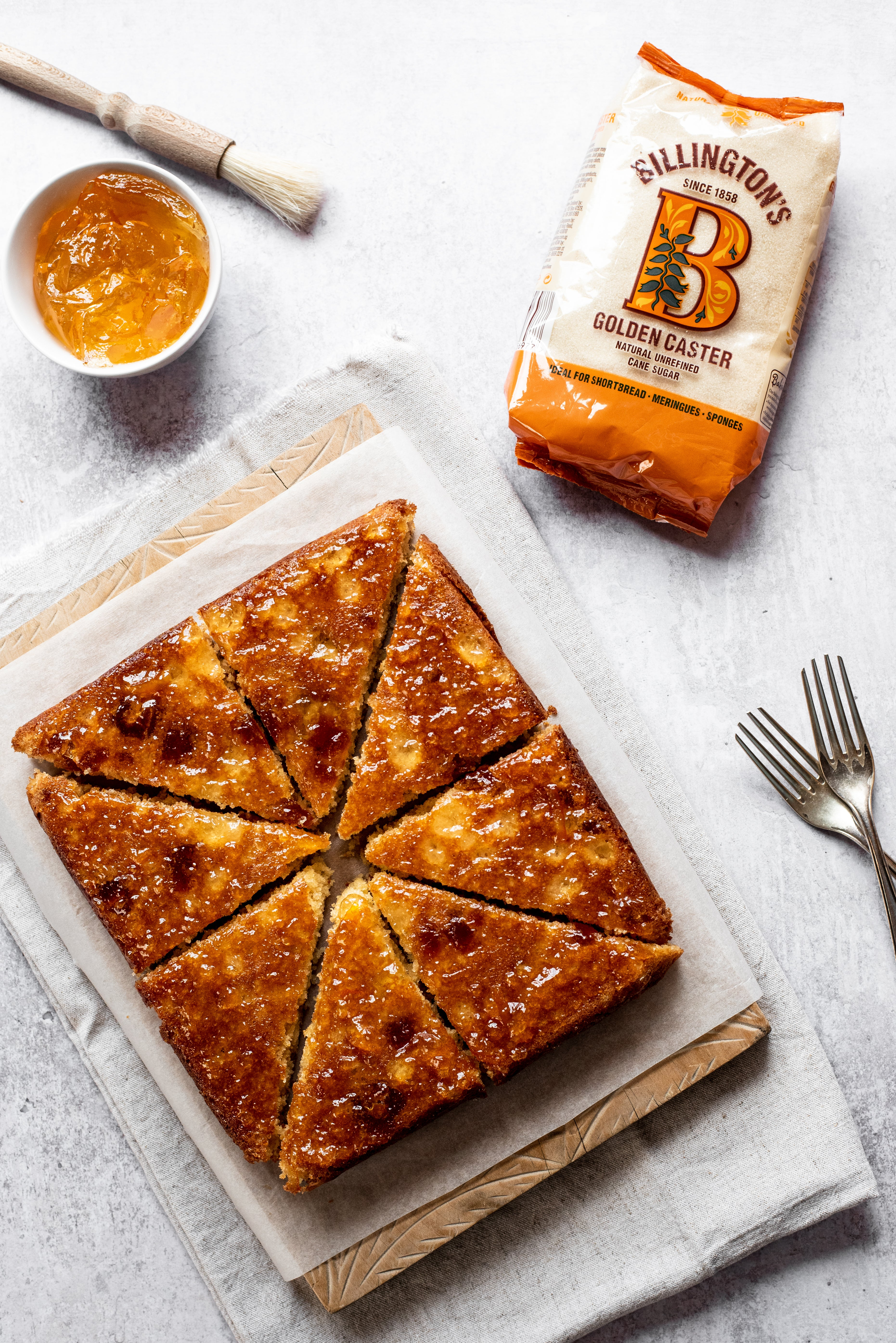 Marmalade Traybake lay on a sheet of baking paper, next to a bag of Billington's Golden Caster sugar and forks