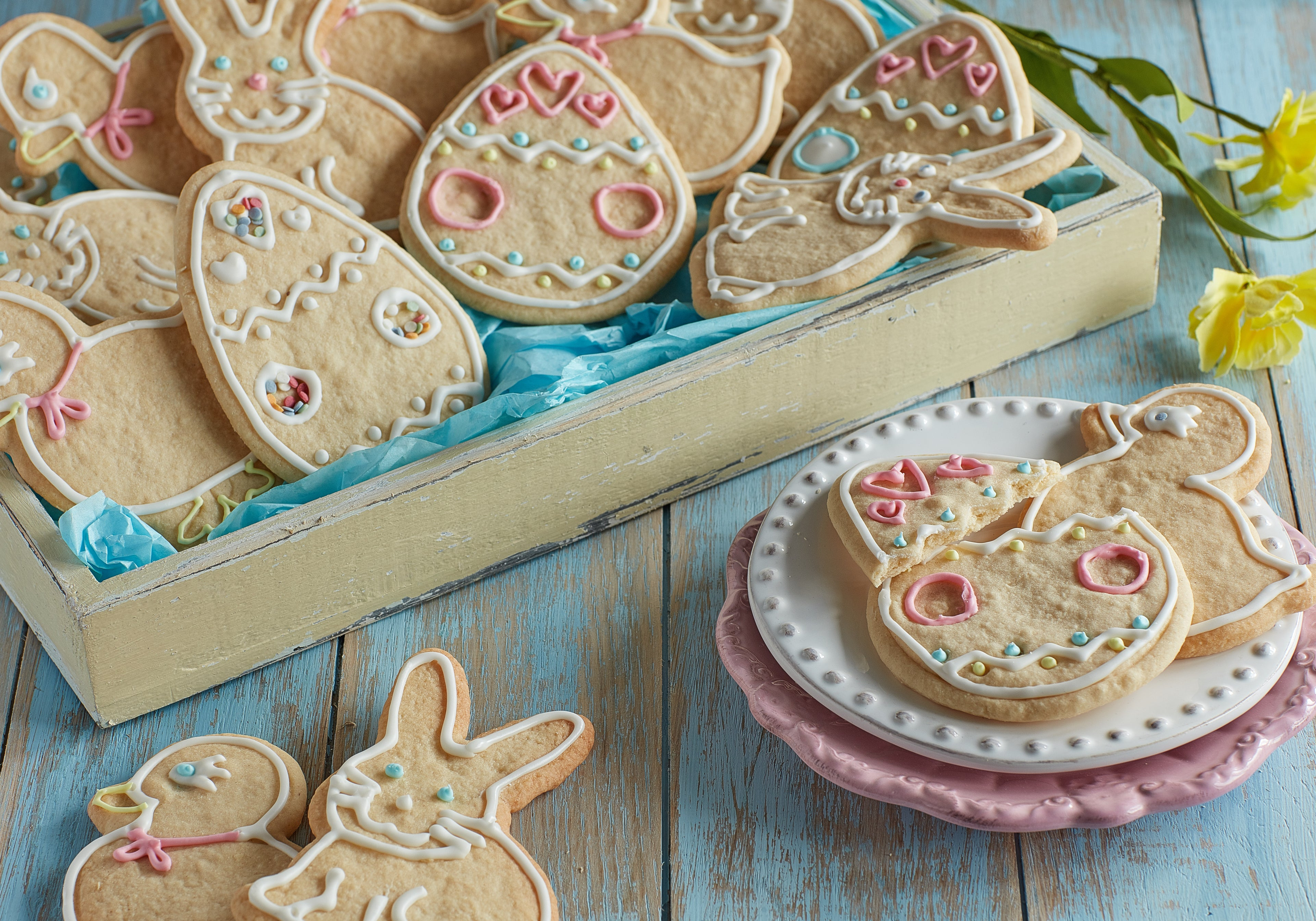 Easter Biscuits in a box with a few on a plate in the forefront
