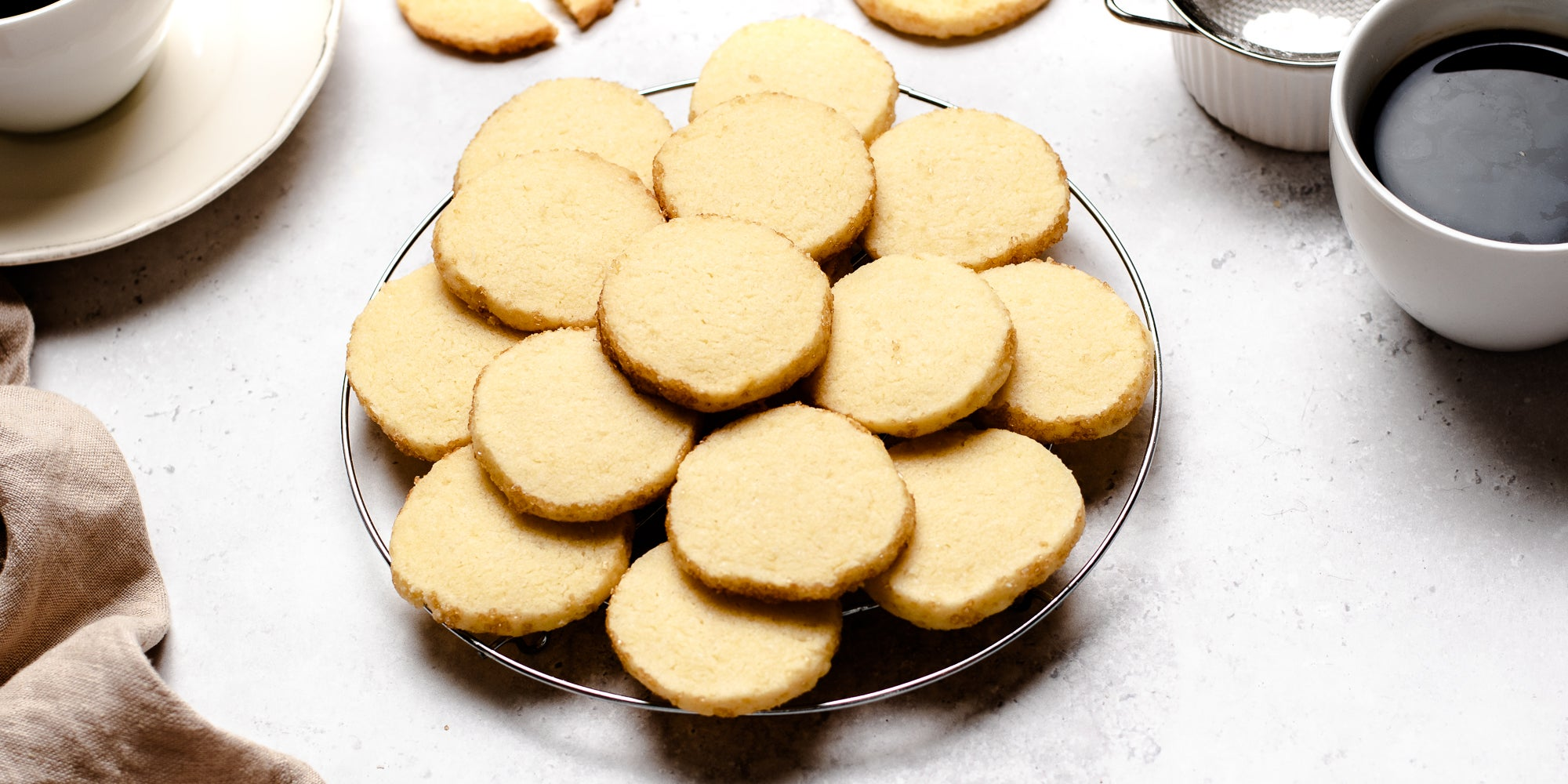 Close up of a batch of fresh biscuits baked from Shortbread Dough on a plate, next to cups and saucers of coffee
