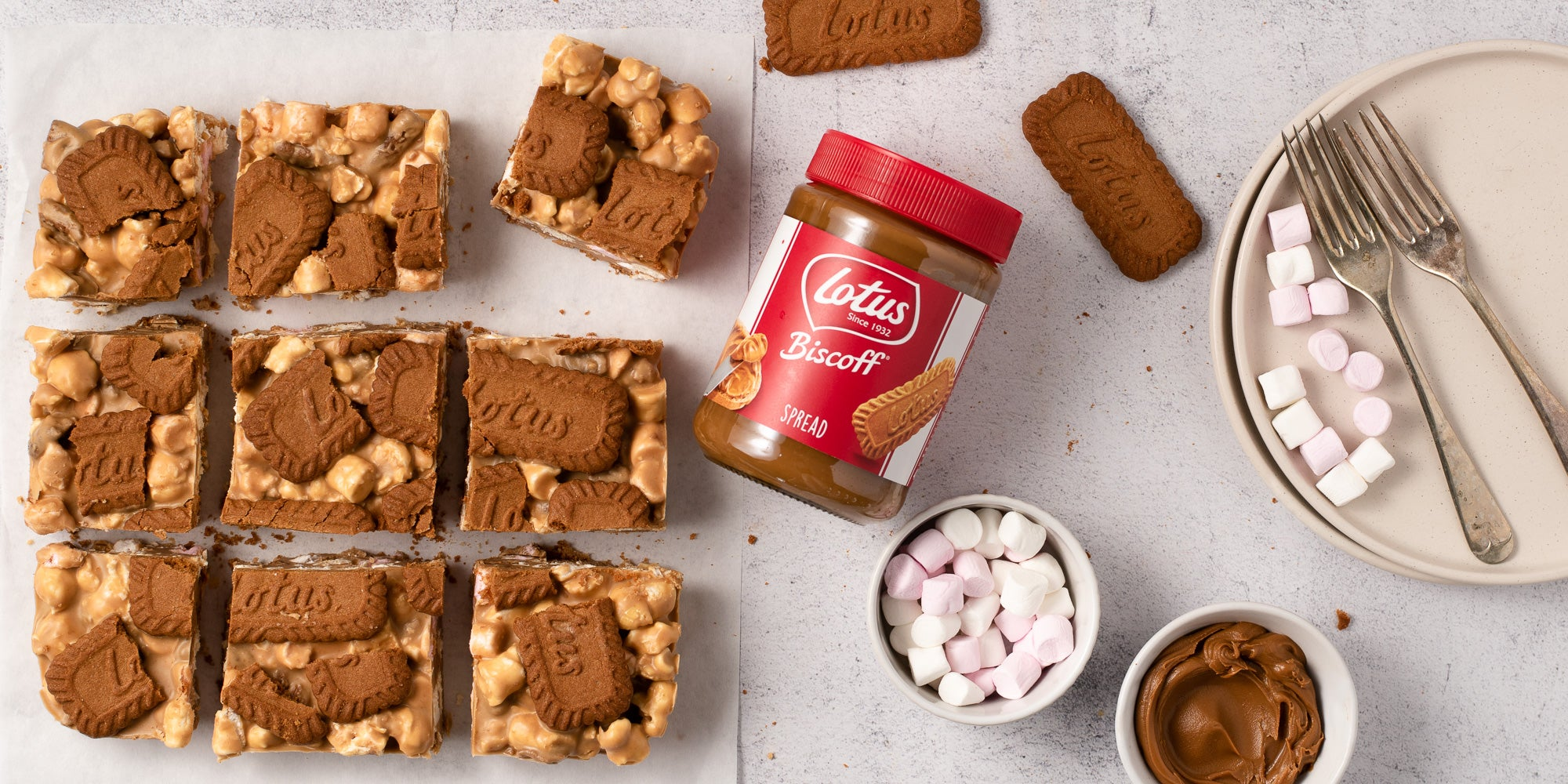 Biscoff rocky road next to lotus biscoff spread and a bowl of marshmallows