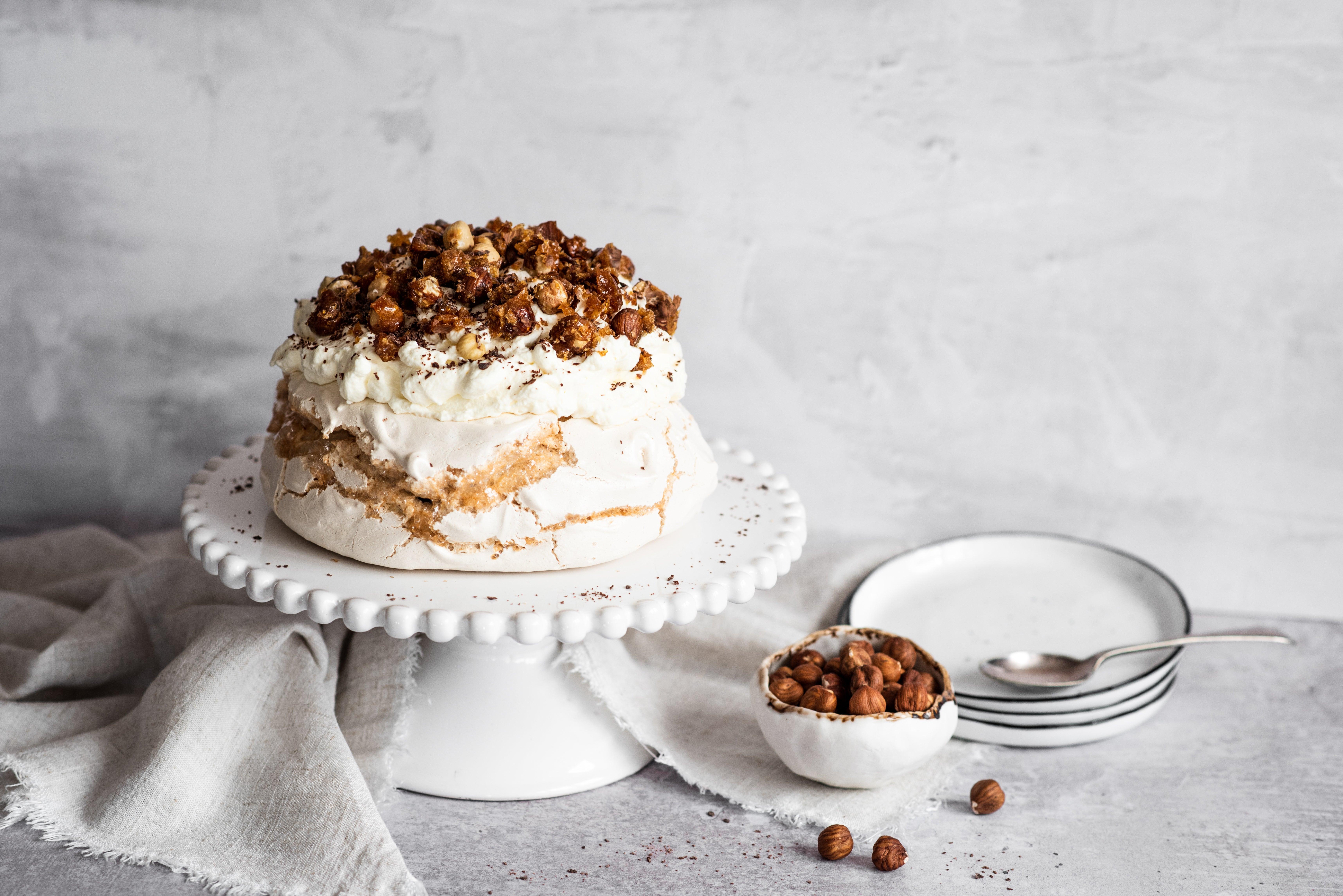 Coffee roasted hazelnut meringue on stand topped with hazelnuts next to a bowl of hazelnuts