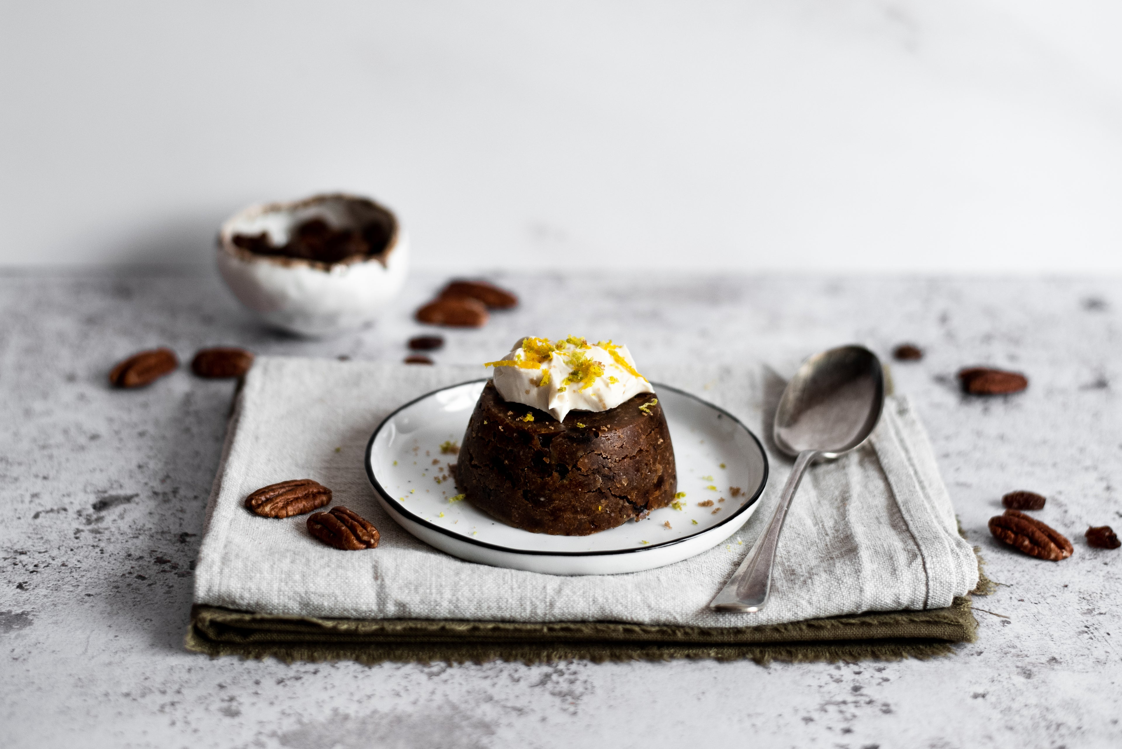 Close up of mini christmas pudding on a plate with a bowl and pecans