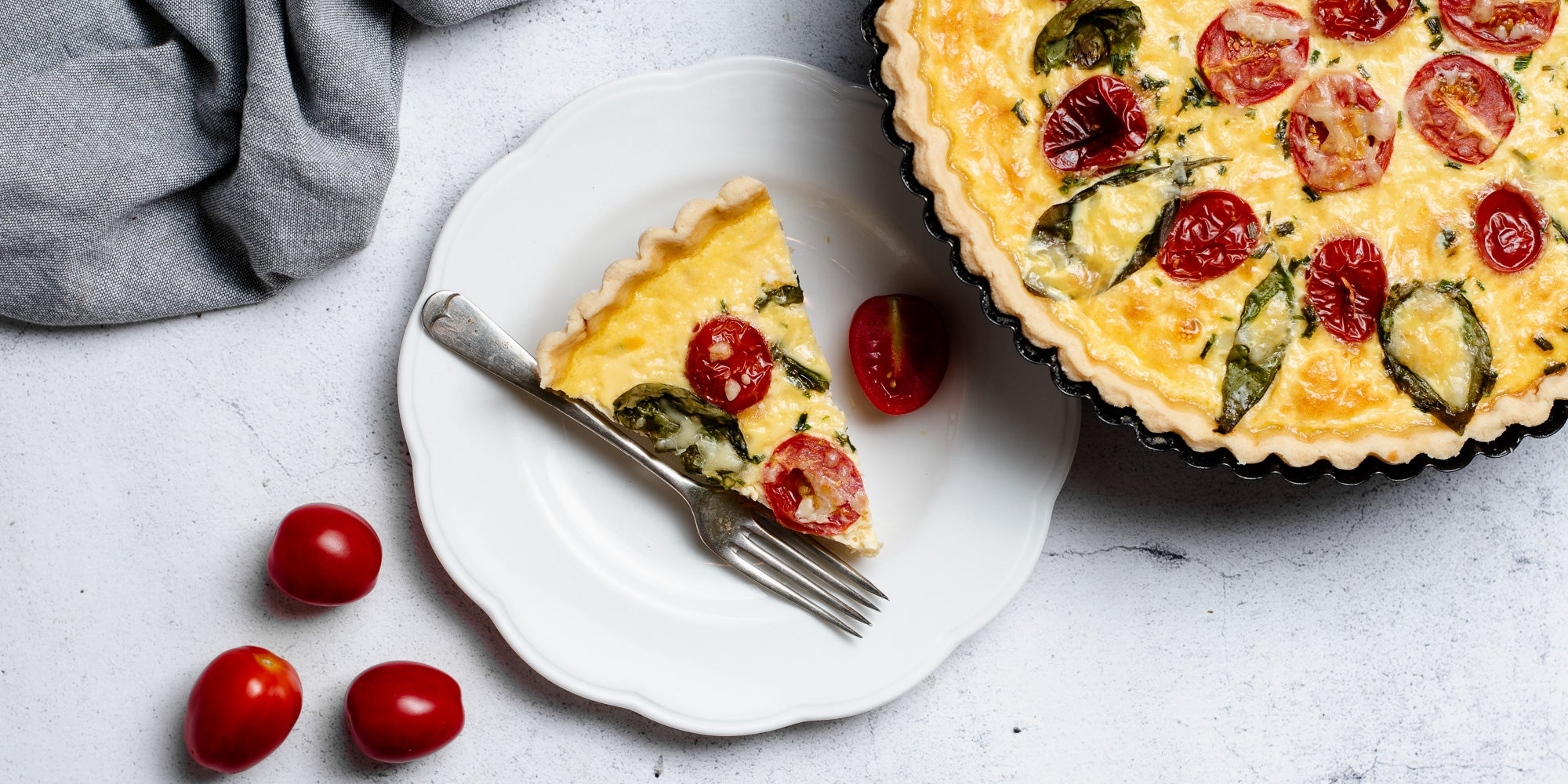 Cheese & Tomato Quiche with a slice on a plate with a fork, next to some chopped tomatoes