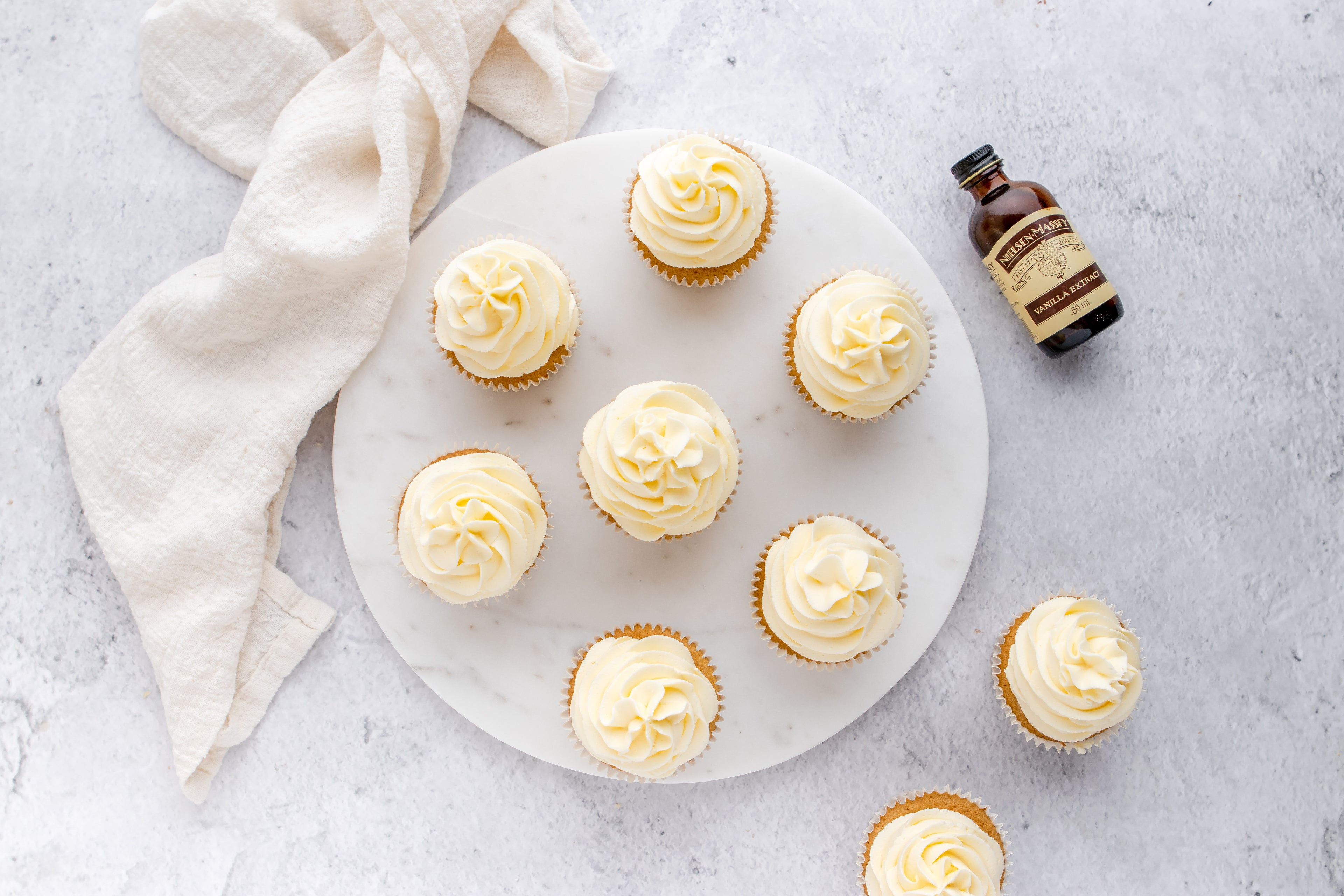 Gluten Free Cupcakes from above view with a bottle of Neilsen-Massey vanilla extract lay next to the serving board