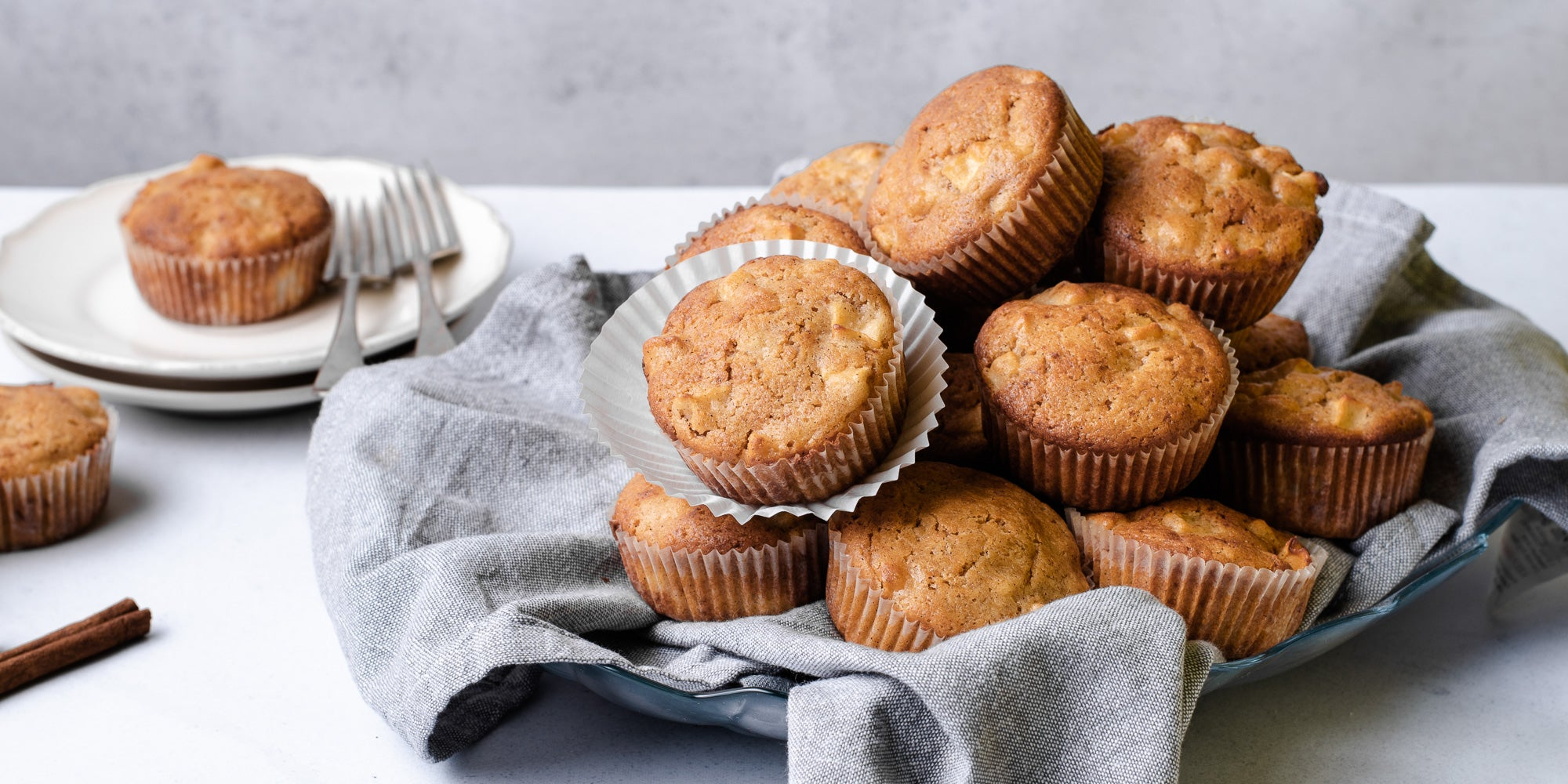 A pile of Calorie Conscious Apple & Cinnamon Muffins on a grey cloth, with a muffin on a plate with forks in the background