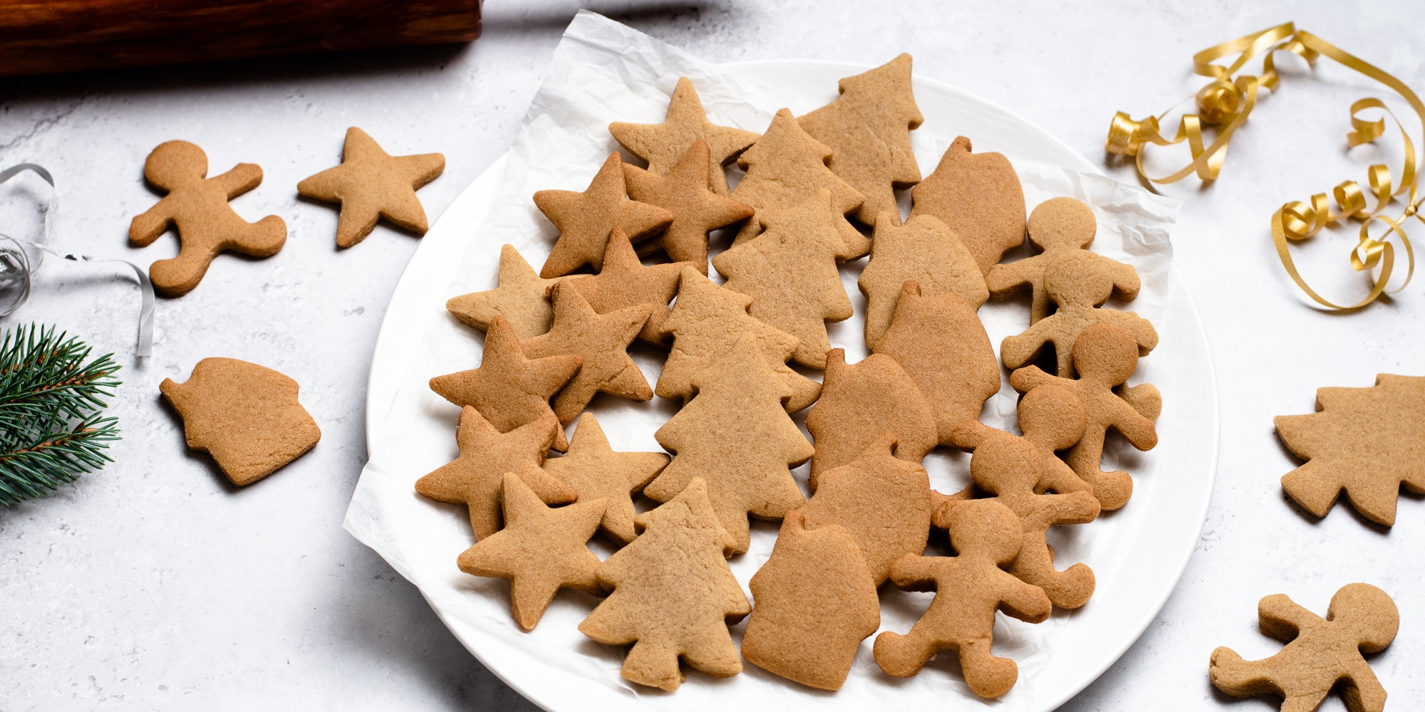 A batch of gingerbread cookies baked from Gingerbread Dough, next to gold ribbon and pine leaves