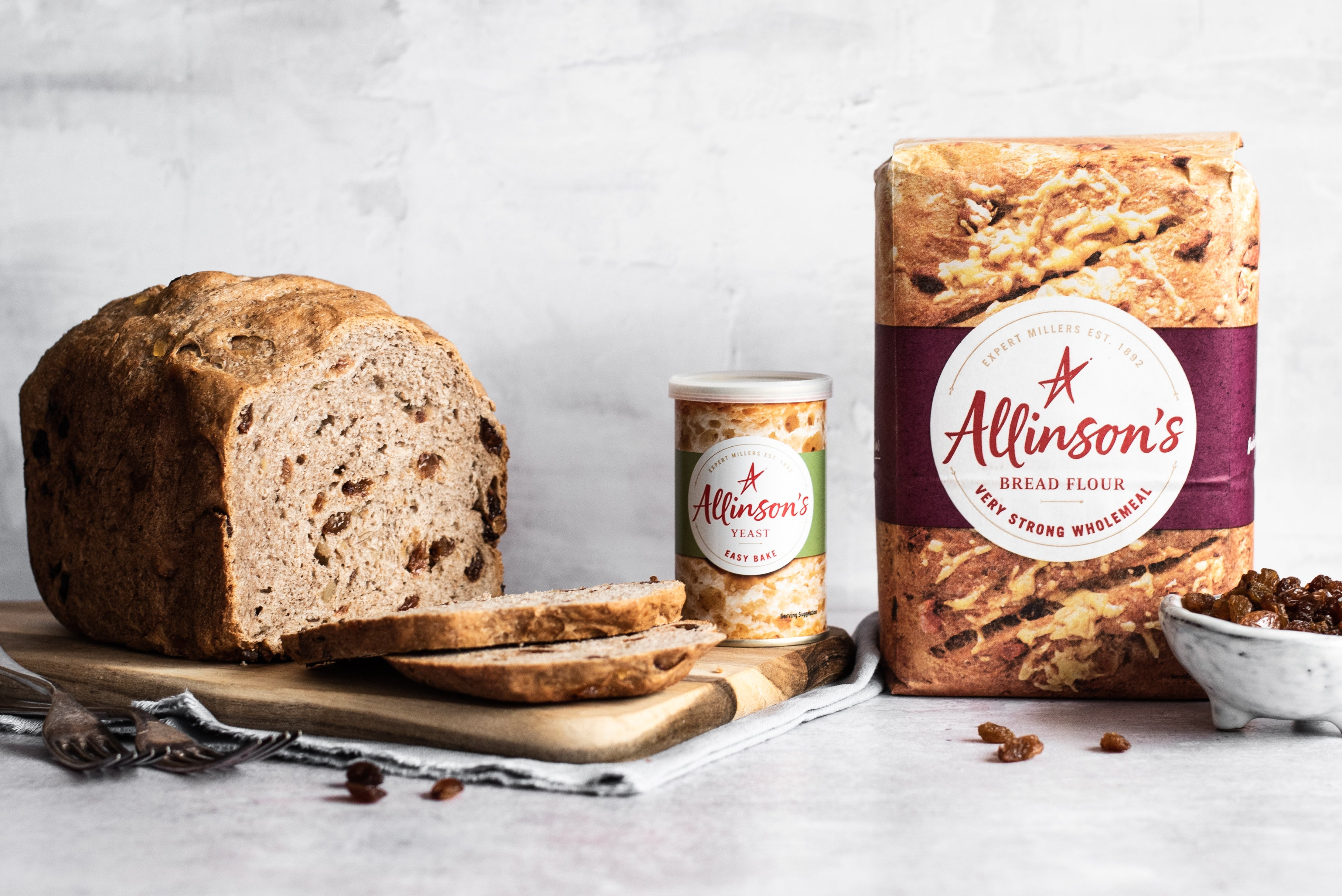 Fruit bread with slices cut infront. Two forks. Tin of yeast. Flour pack. Bowl of sultanas