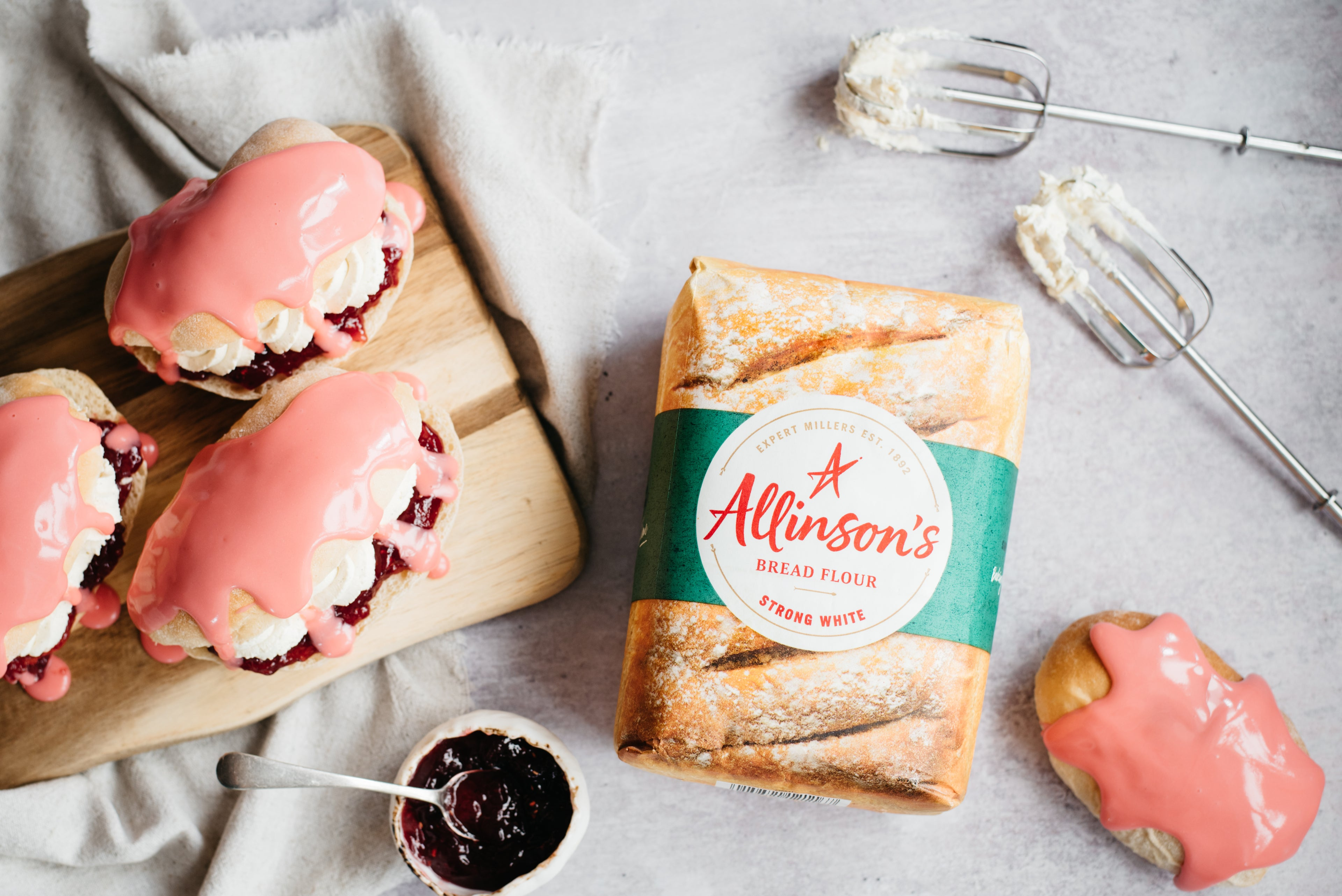 Flat lay of Iced Finger Buns drizzled in pink icing, next to a bag of Allinson's strong white flour, and whisks covered in mixture