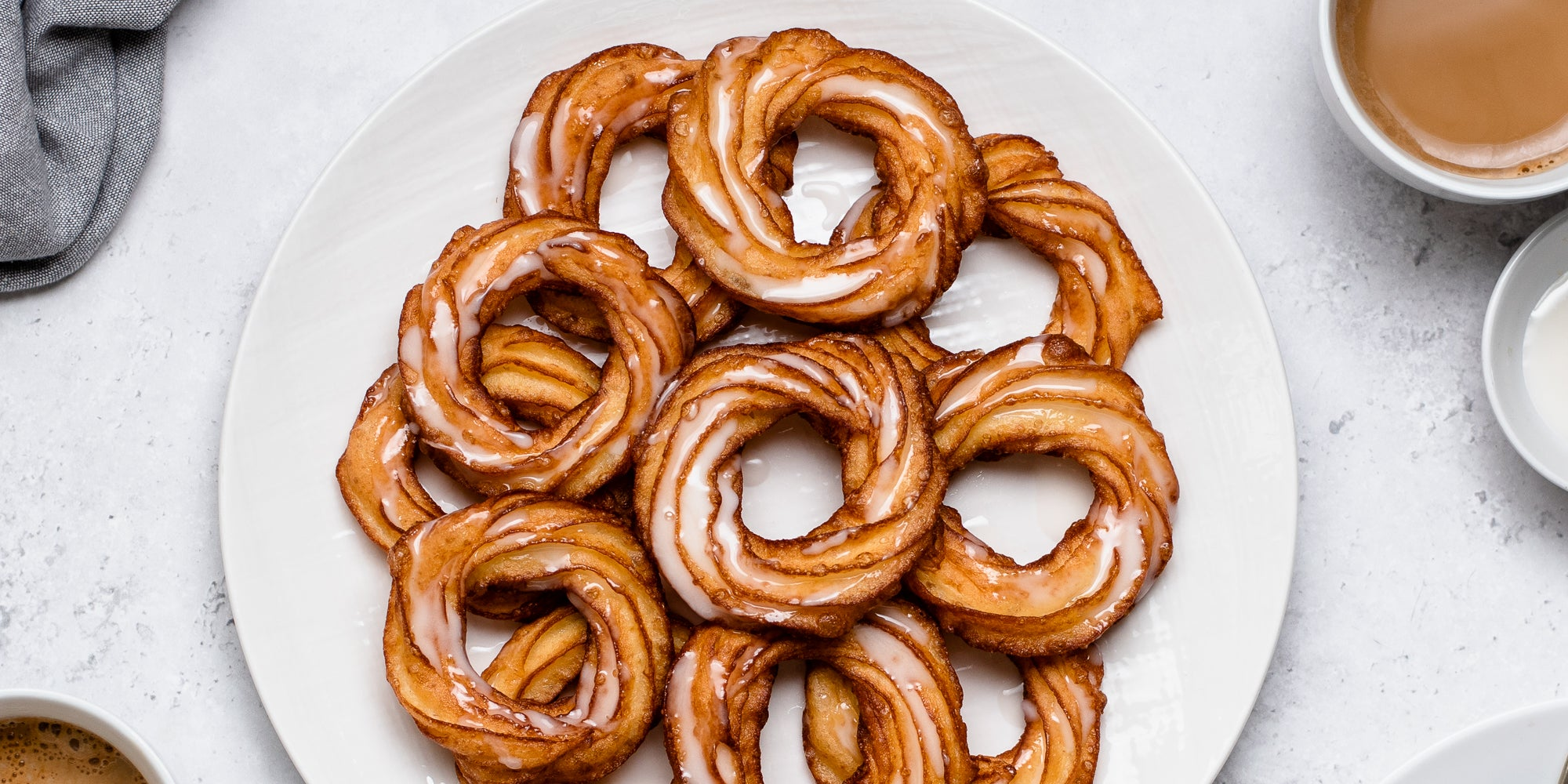 Close up top view of Apple Cider Crullers on a plate, drizzled with icing