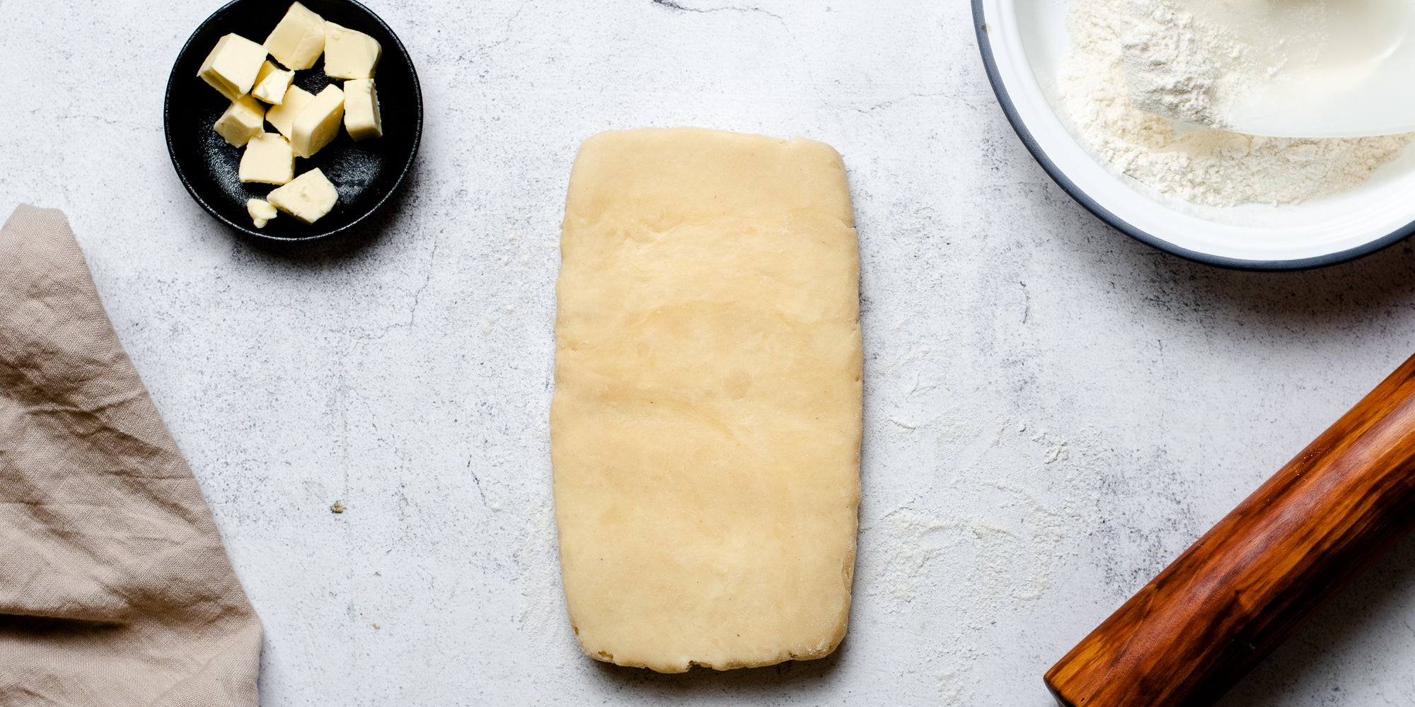 Puff Pastry rolled out onto a surface next to a dish of butter, bowl of flour and rolling pin