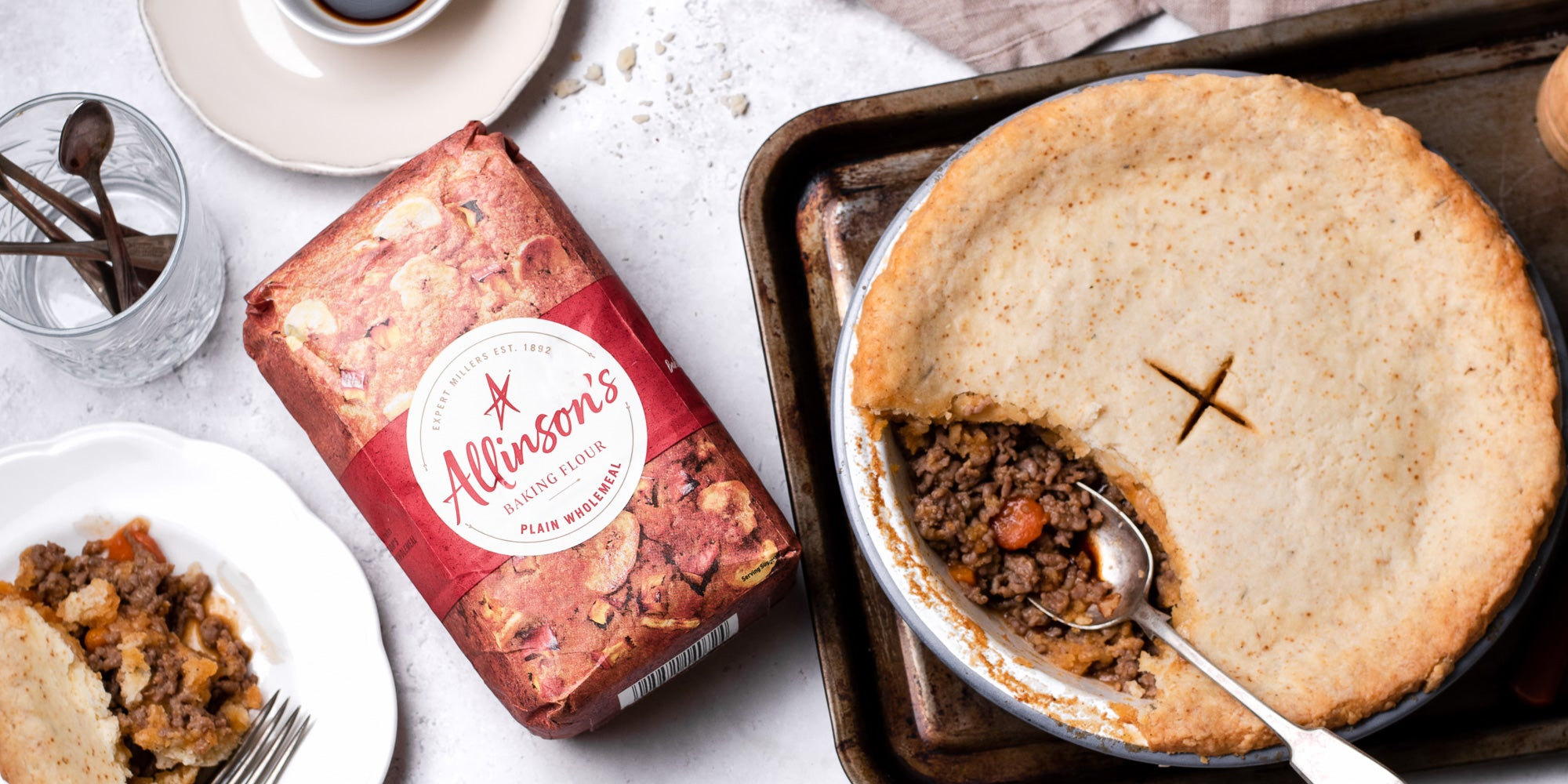 Suet Crusted Beef & Onion Pie on a baking tray, with a spoon serving some of the pie filling. Next to a bag of Allinson's Plain Wholemeal flour and a plate with a serving of pie.