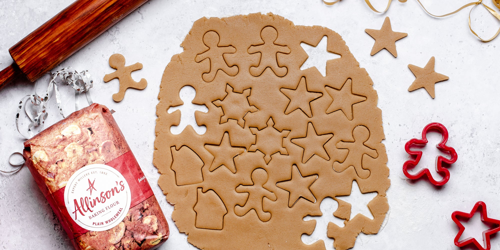Top view of rolled out Gingerbread Dough, with shapes cut out of it, next to cookie cutters and a bag of Allinson's plain flour